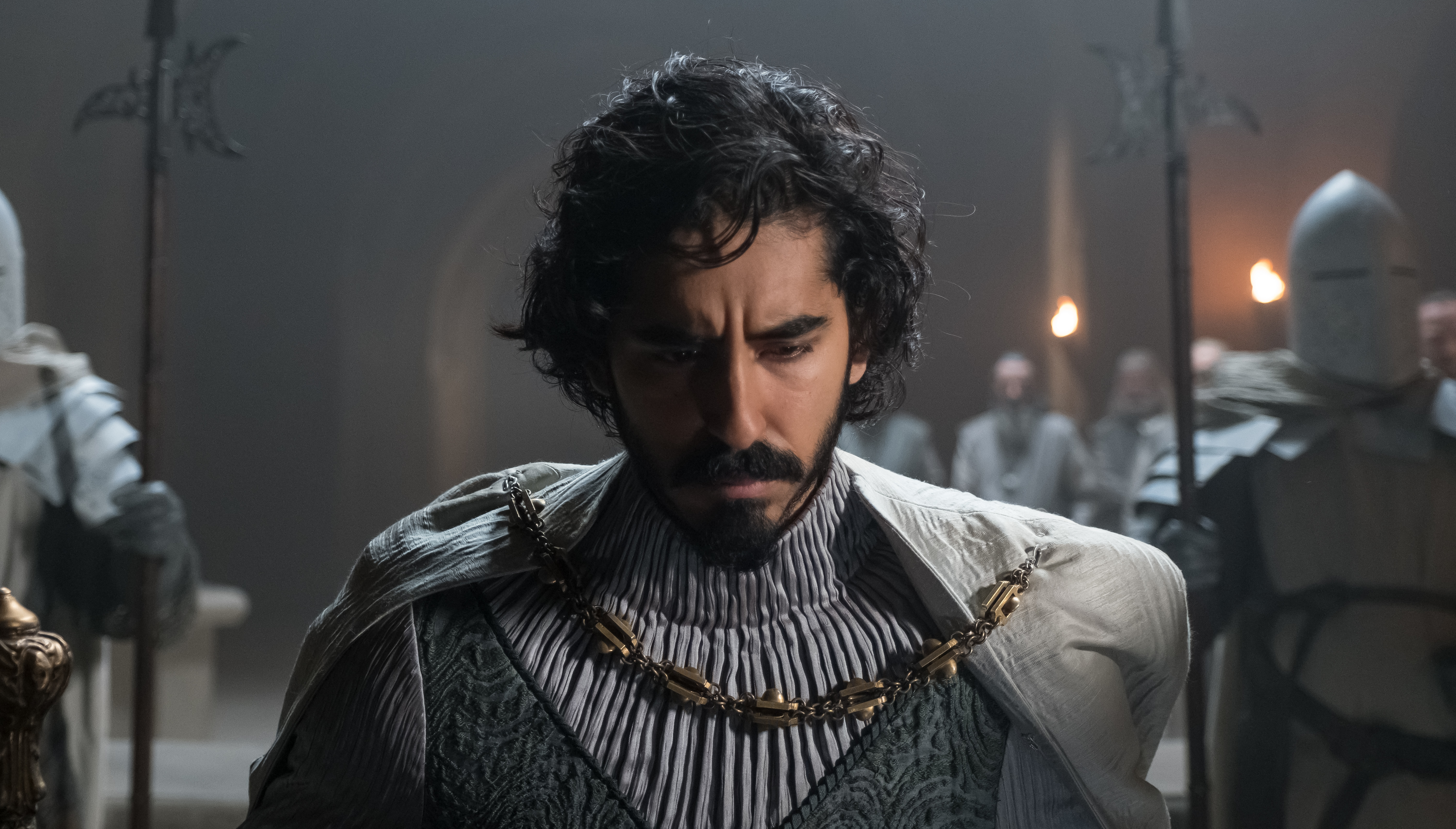 Dev Patel, in grey armor with his head bowed, in The Green Knight