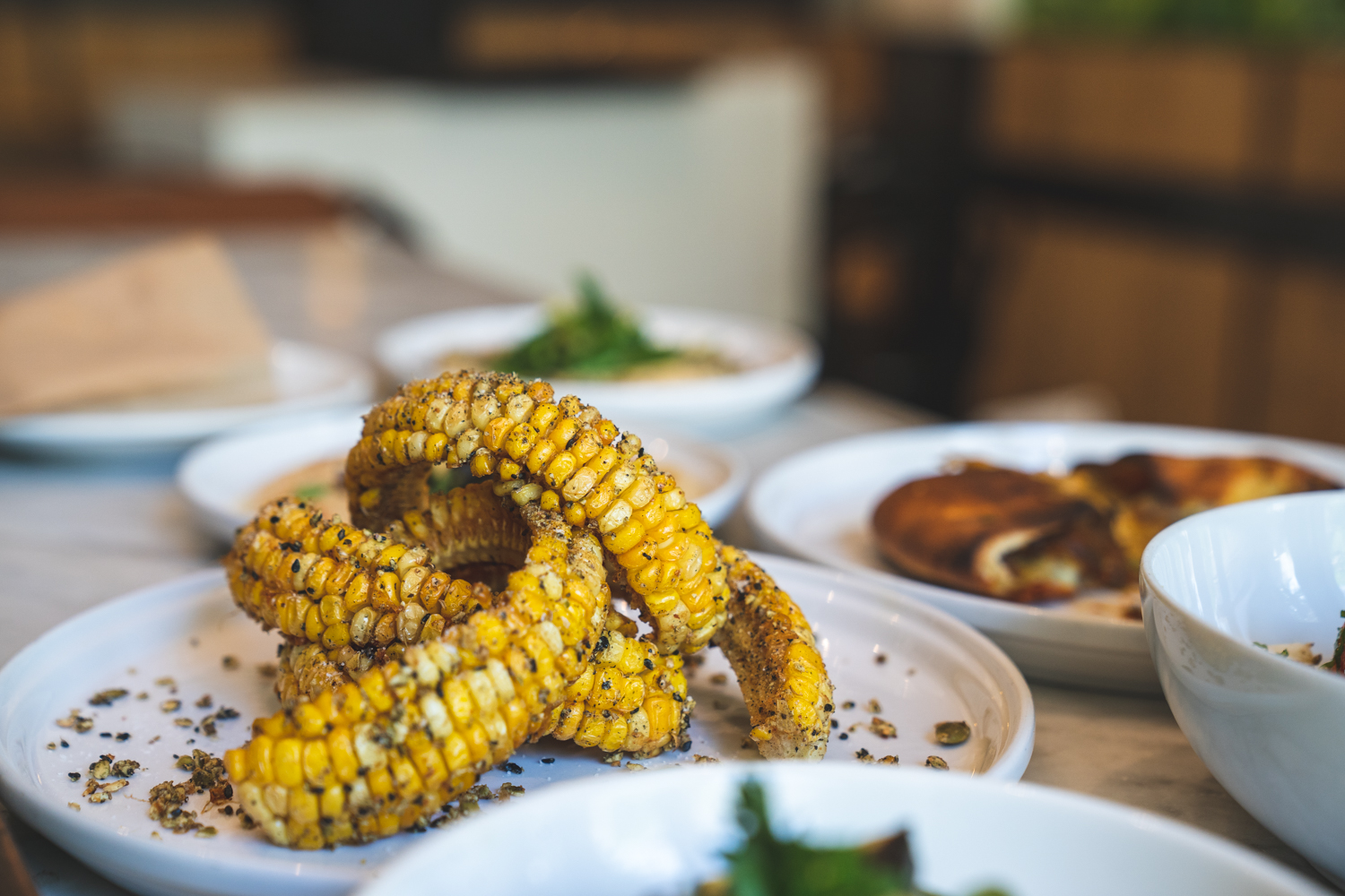 A plate of corn ribs sits next to various bowls and plates at Lil Shalom in Portland, Oregon