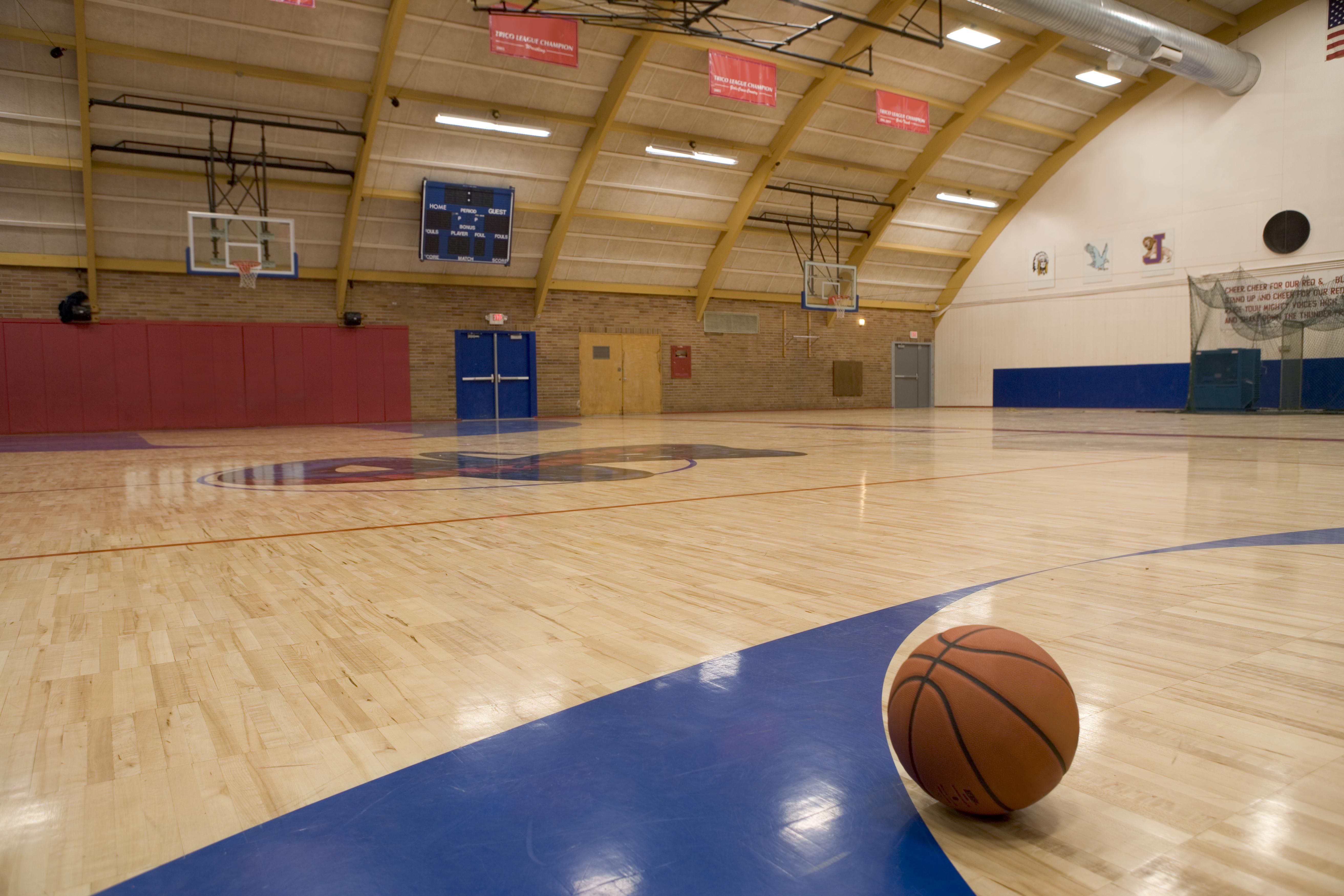 A basketball on a gym floor.