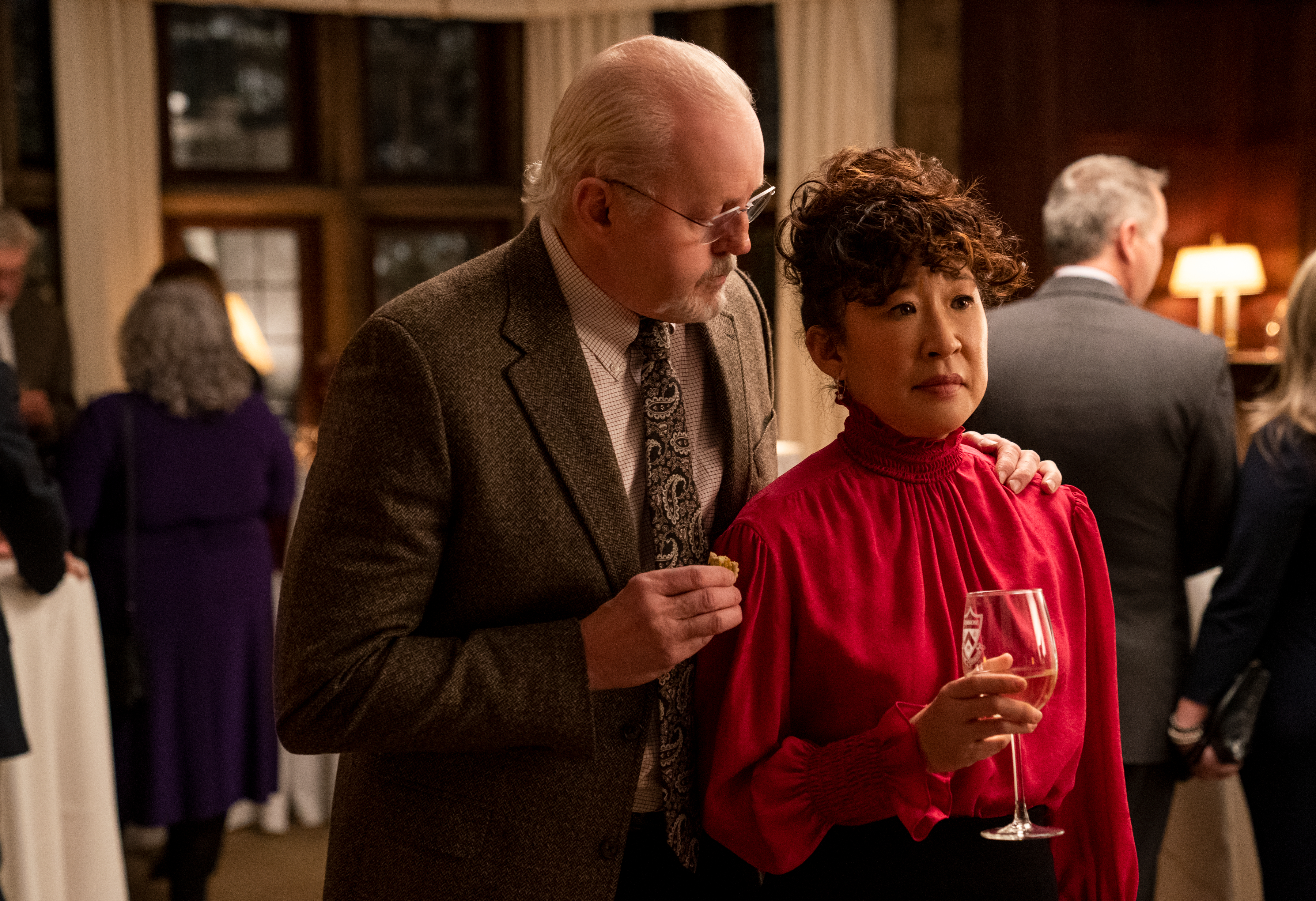 David Morse as the college dean puts his hand on Sandra Oh's shoulder at an awkward faculty party in Netflix's The Chair