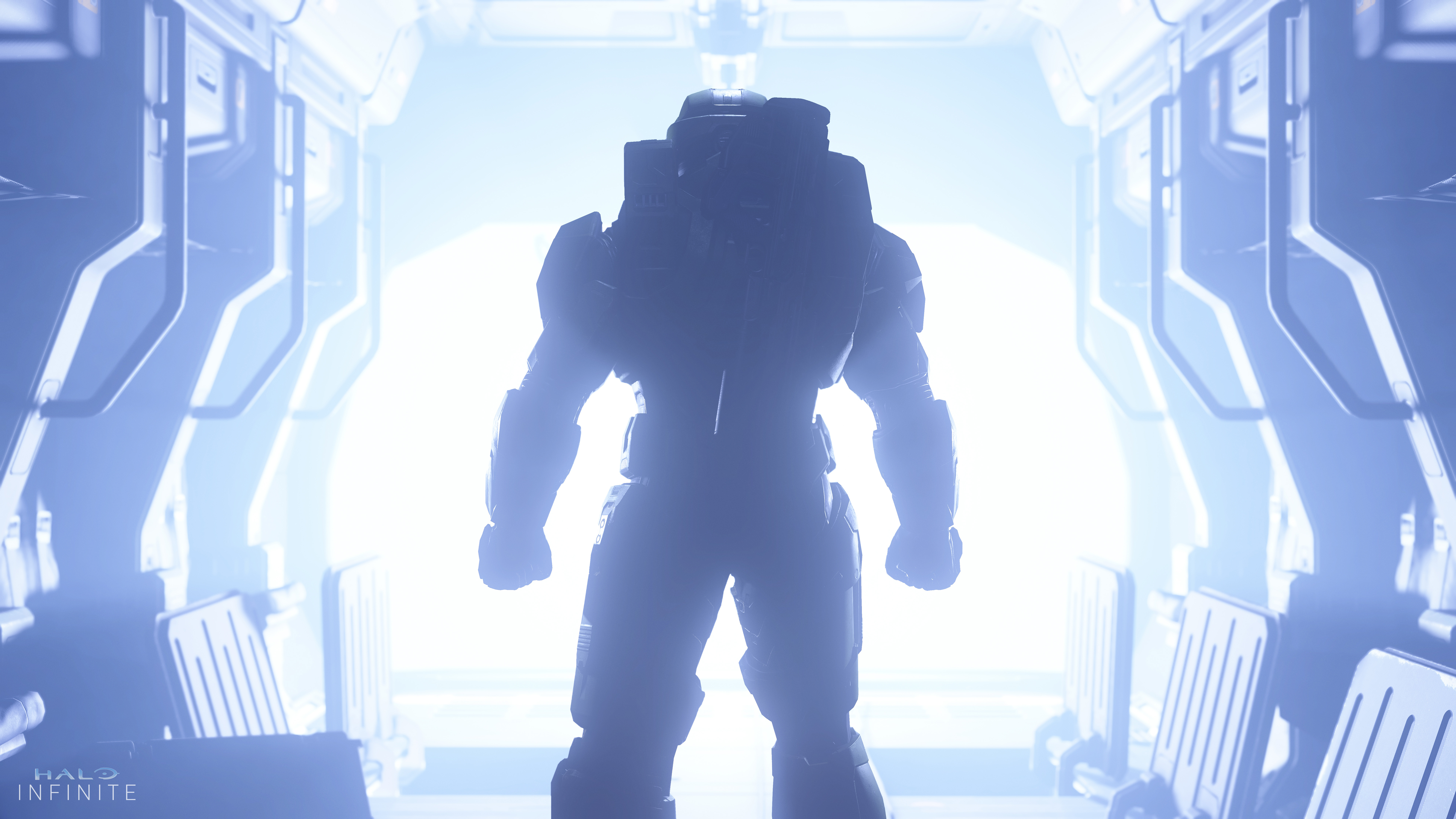 an image of Master Chief from behind, standing at the opening of a spaceship bay with blue light flooding in, in Halo Infinite