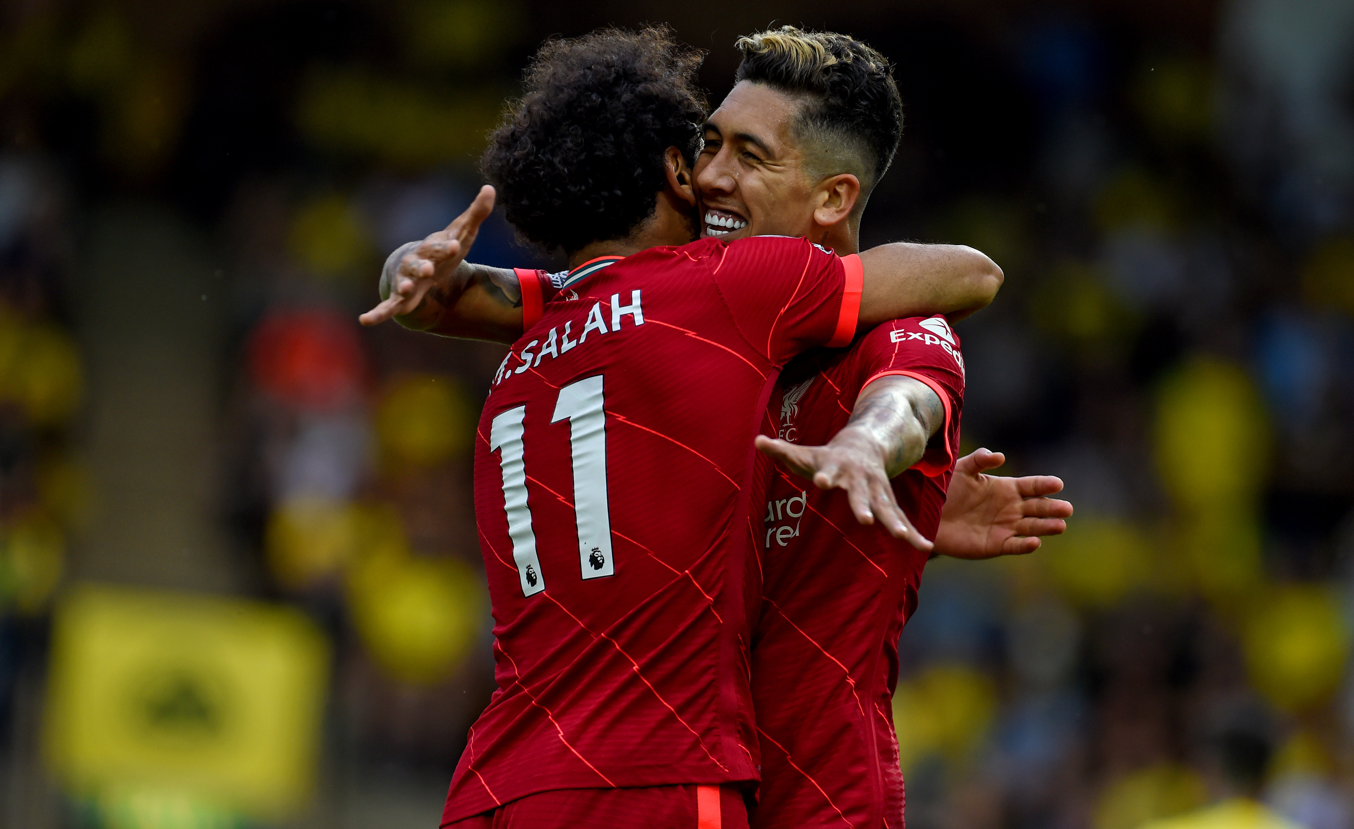 Roberto Firmino celebrates after scoring the second goal with Mohamed Salah of Liverpool during the Premier League match between Norwich City and Liverpool at Carrow Road on August 14, 2021 in Norwich, England.