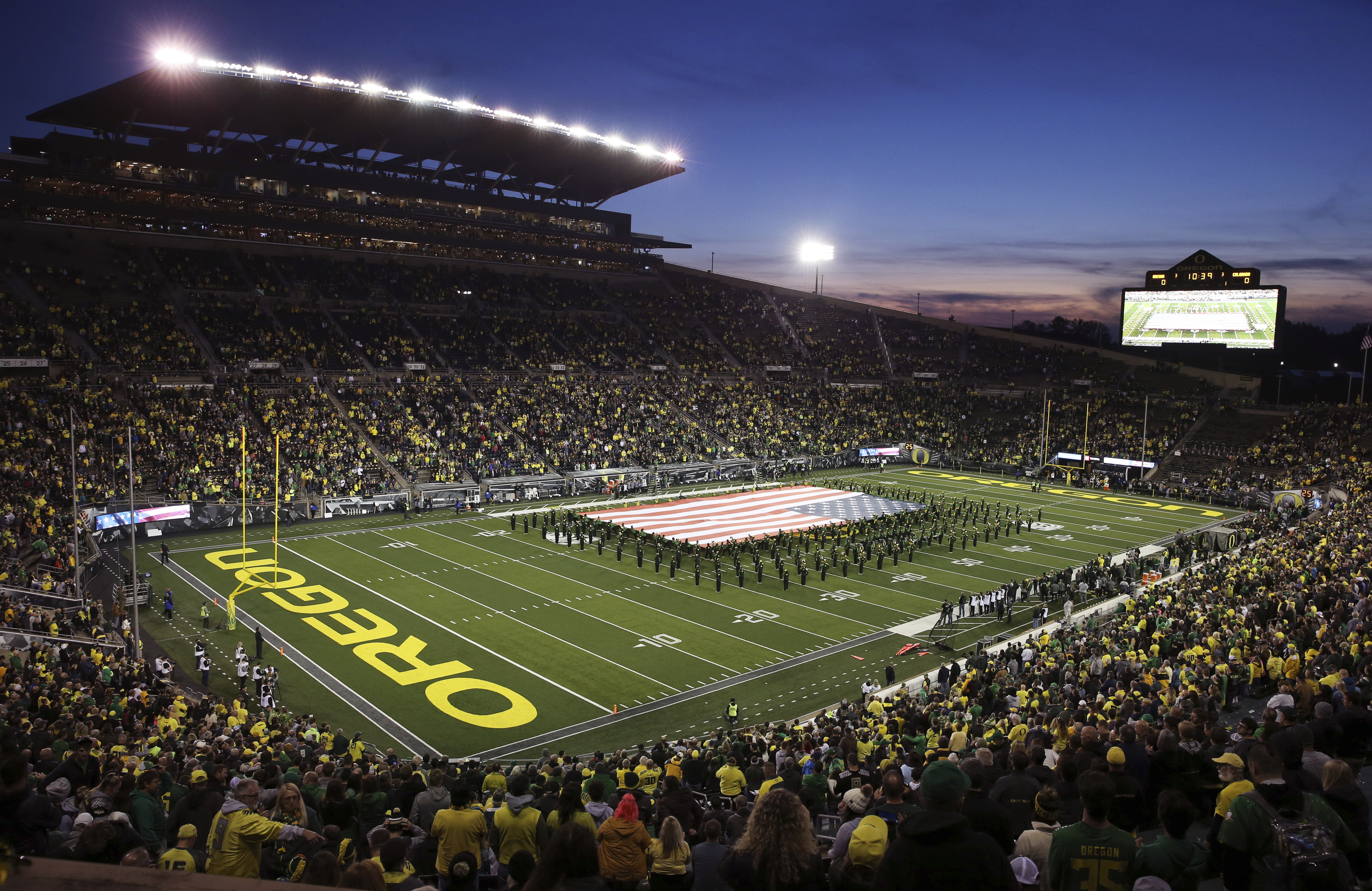 The Oregon Marching Band displays a giant U.S. flag on the field at Autzen Stadium before a football game against Colorado.