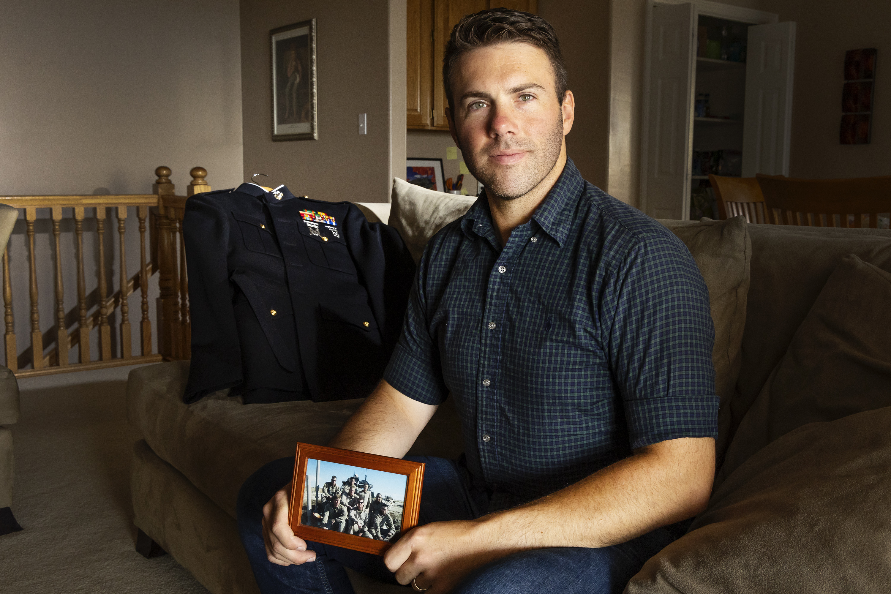 Jeremy Ruppe, a Marine who served with the 4th Light Armored Reconnaissance Battalion in Afghanistan, holds a photo of his crew in Afghanistan while posing for photos at his home in Lindon on Friday, Aug. 20, 2021.