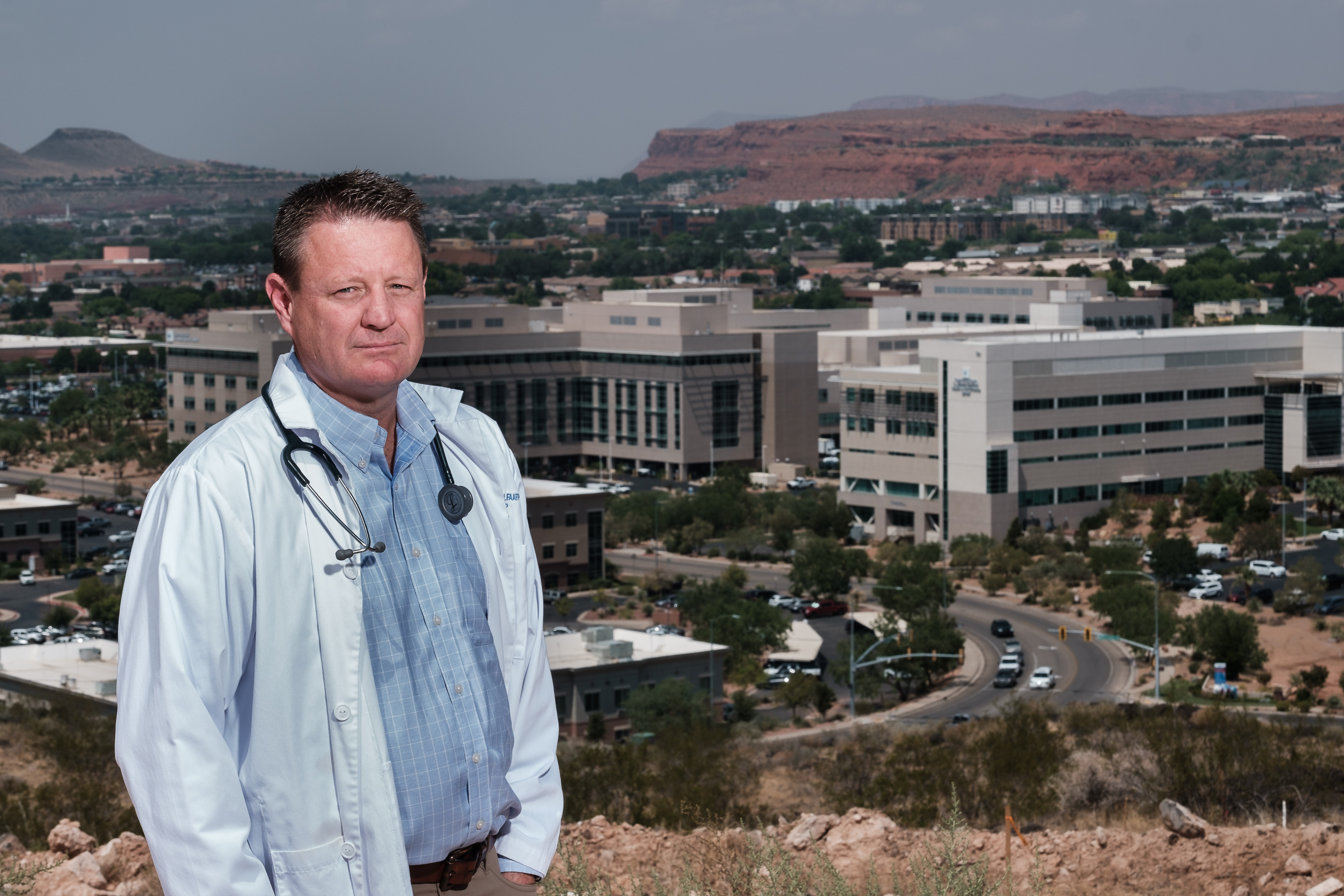 Dr. David Grygla, hospitalist at a St. George hospital, poses for a portrait with the St. George skyline behind him.