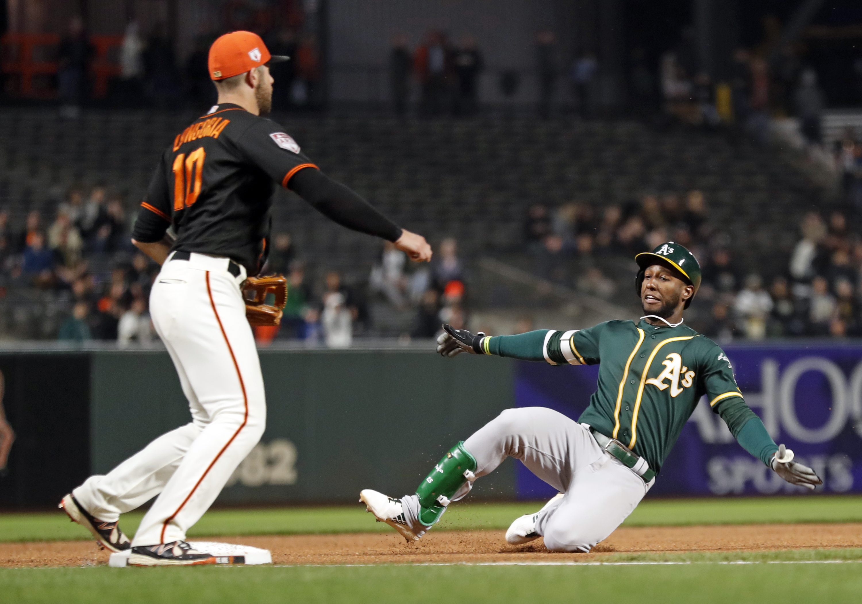 Oakland Athletics' Jurickson Profar slides into third base with a triple as San Francisco Giants' Evan Longoria awaits the throw in 4th inning of Bay Bridge Series game at Oracle Park in San Francisco, Calif., on Tuesday, March 26, 2019.