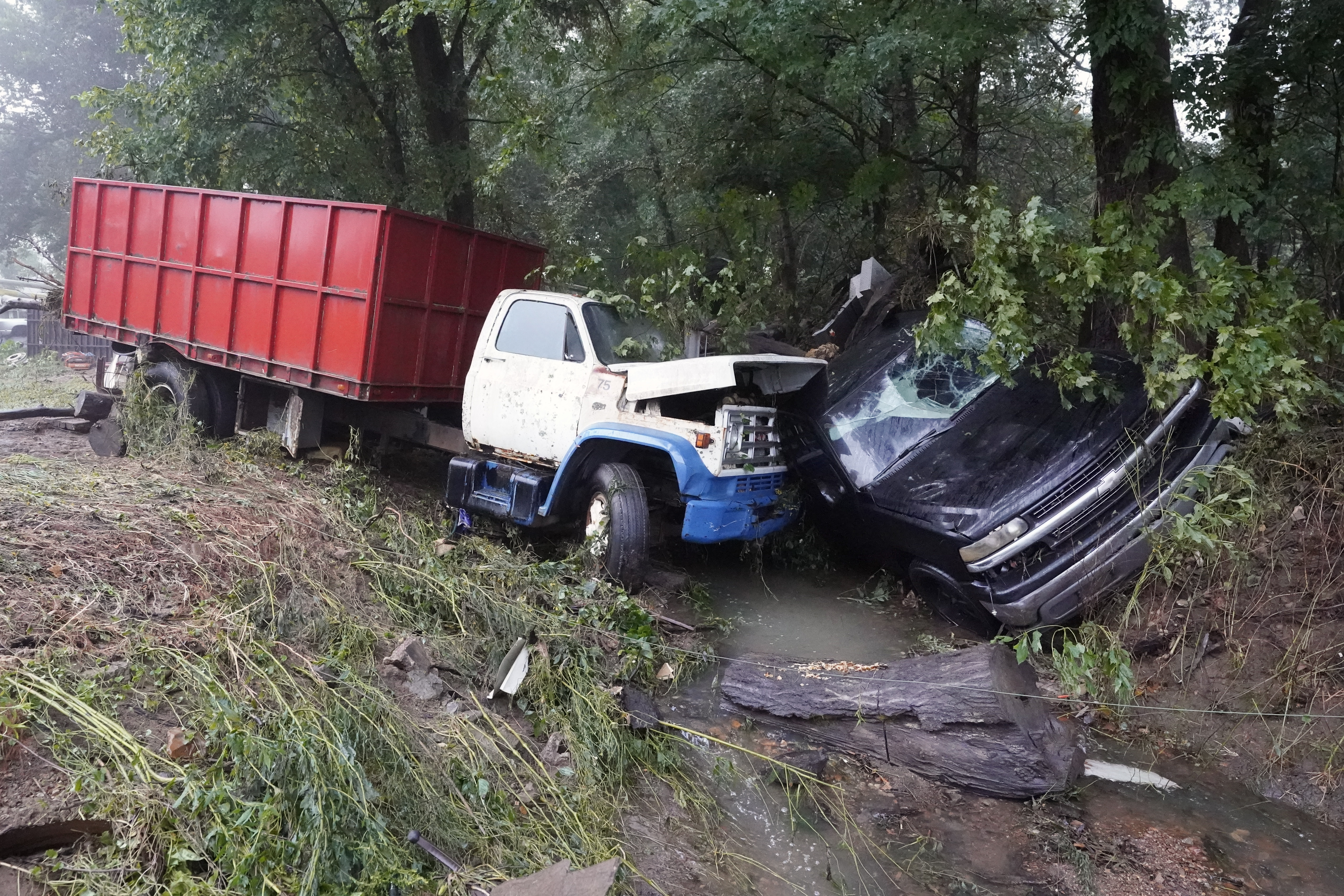 A truck and a car sit in a creek Sunday, Aug. 22, 2021, after they were washed away the day before in McEwen, Tenn. Heavy rains caused flooding in Middle Tennessee and have resulted in multiple deaths as homes and rural roads were washed away.