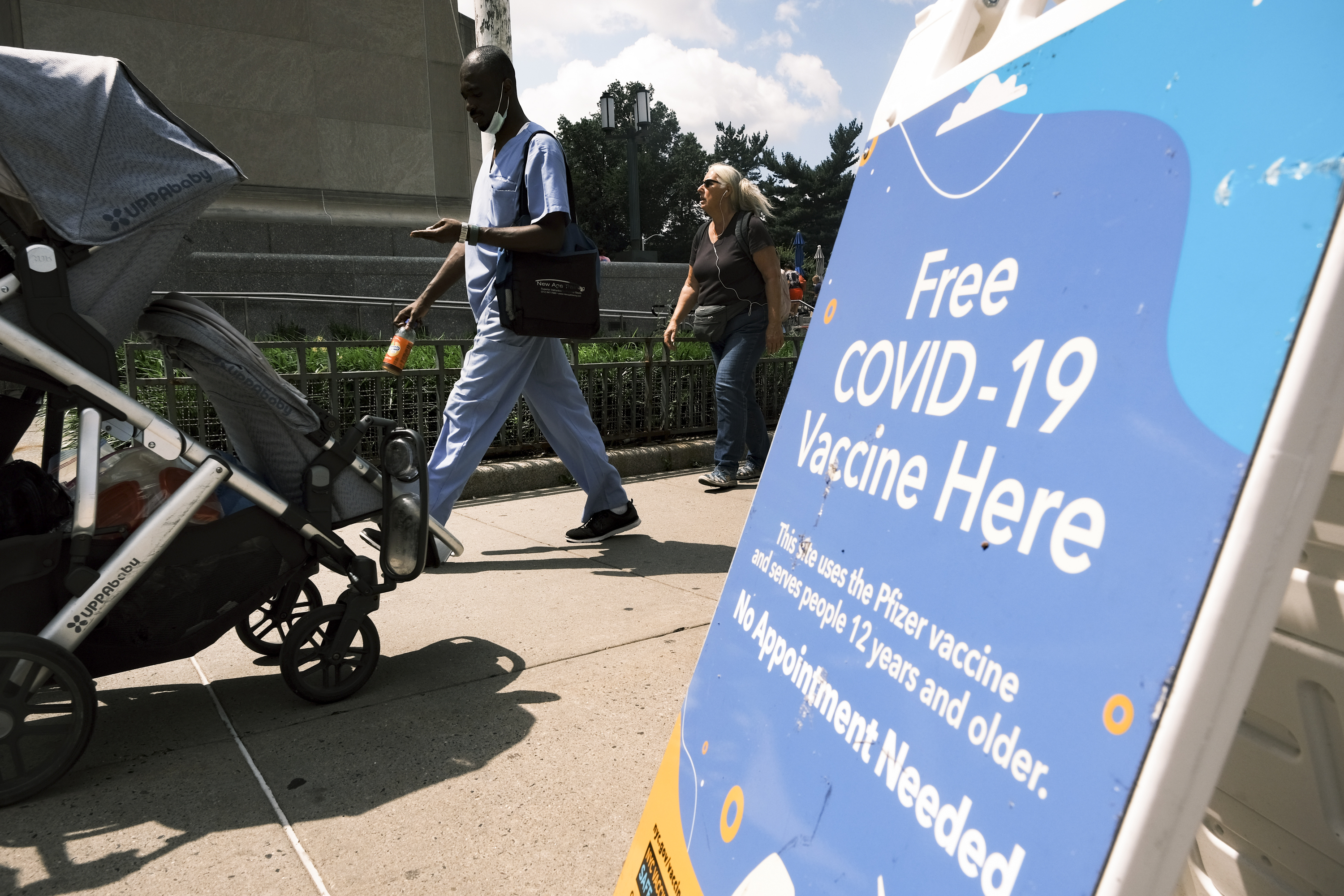 """Pedestrians, one pushing a stroller, walk past a sidewalk sign that reads, """"Free Covid-19 vaccine here."""""""