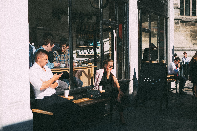 Customers sit outside Rosslyn Coffee in London in 2018