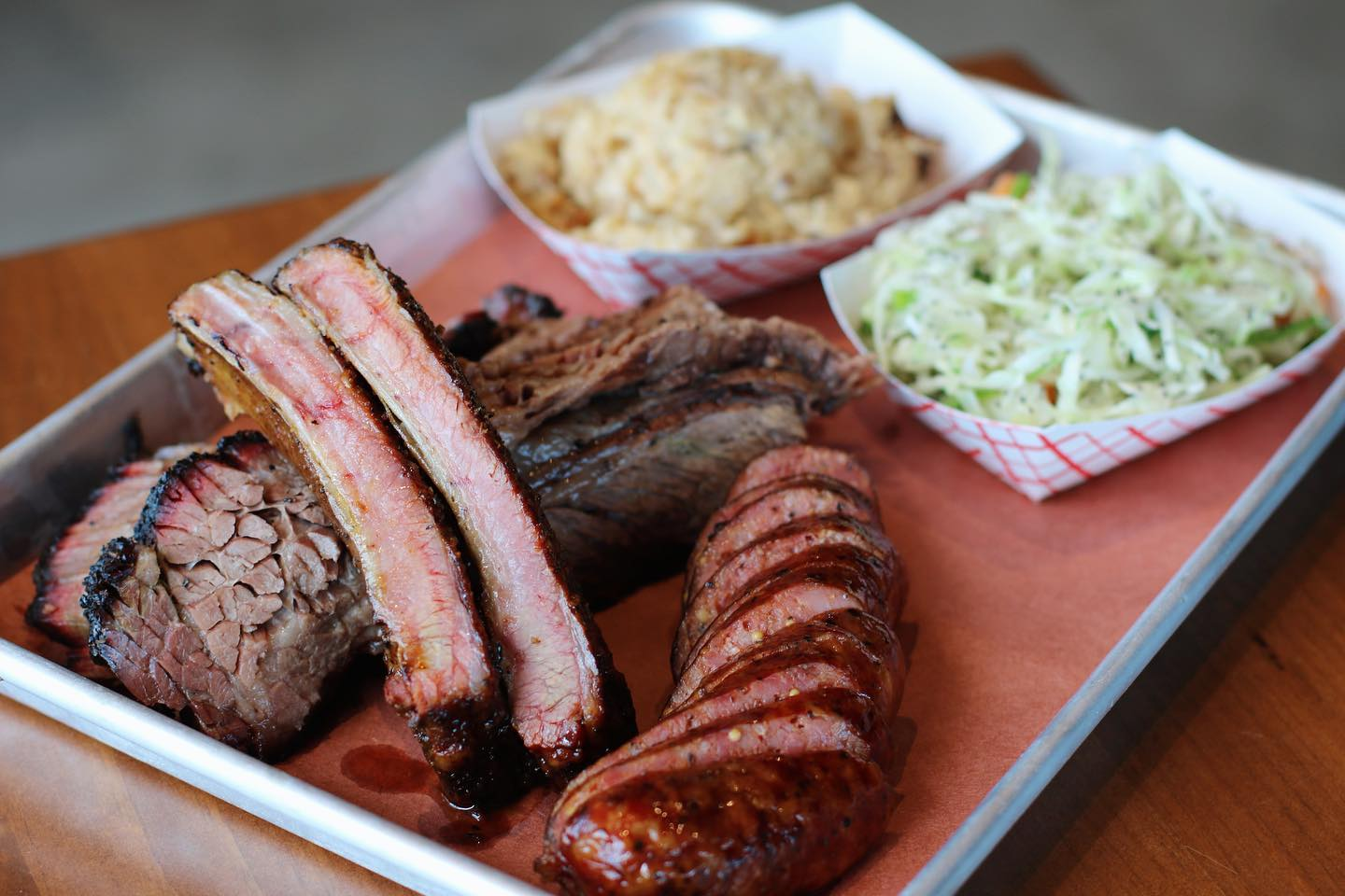 brisket, ribs and sausage on a platter with two sides