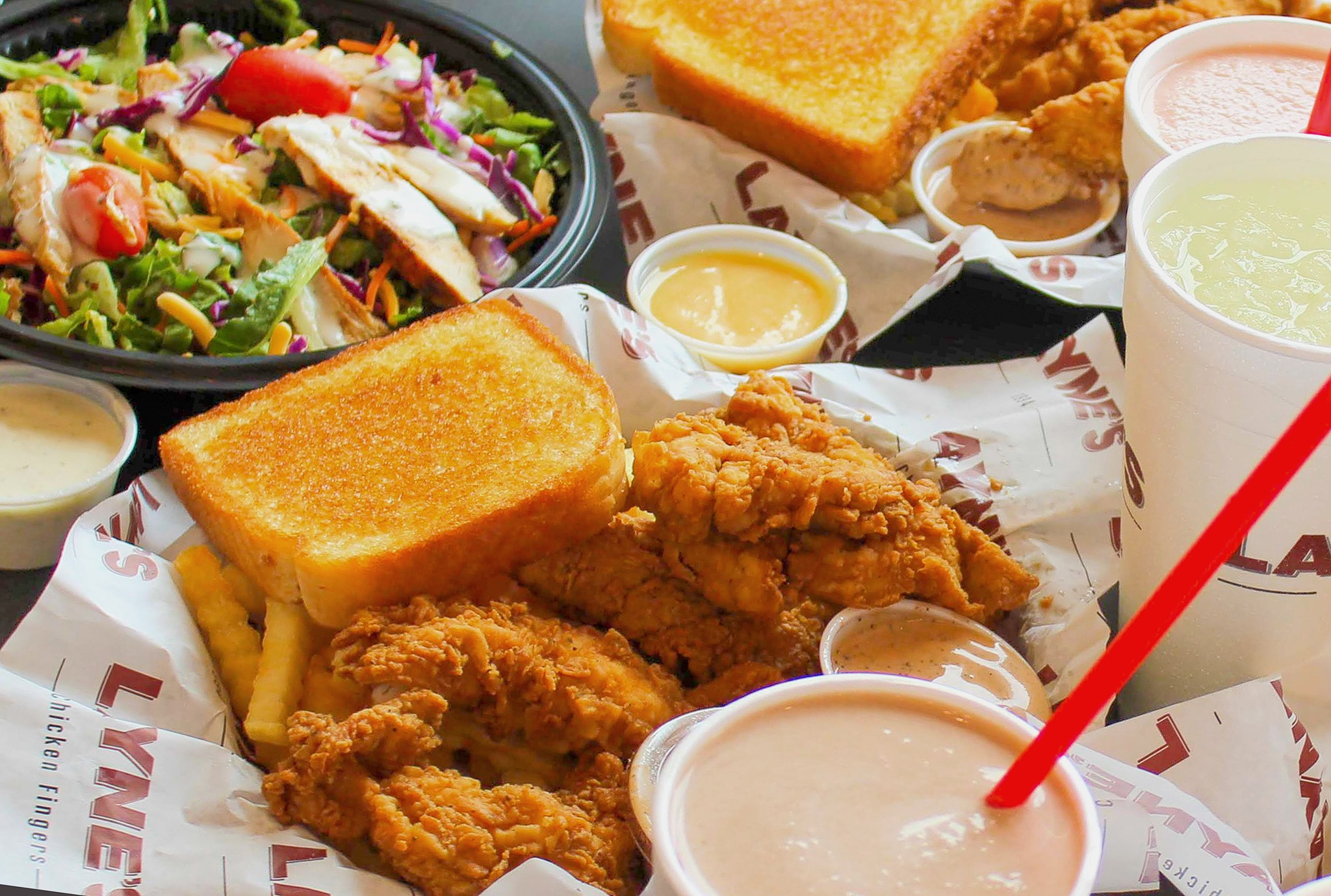 A basket of chicken tenders served with Texas toast and a milkshake. A salad sits in the background.