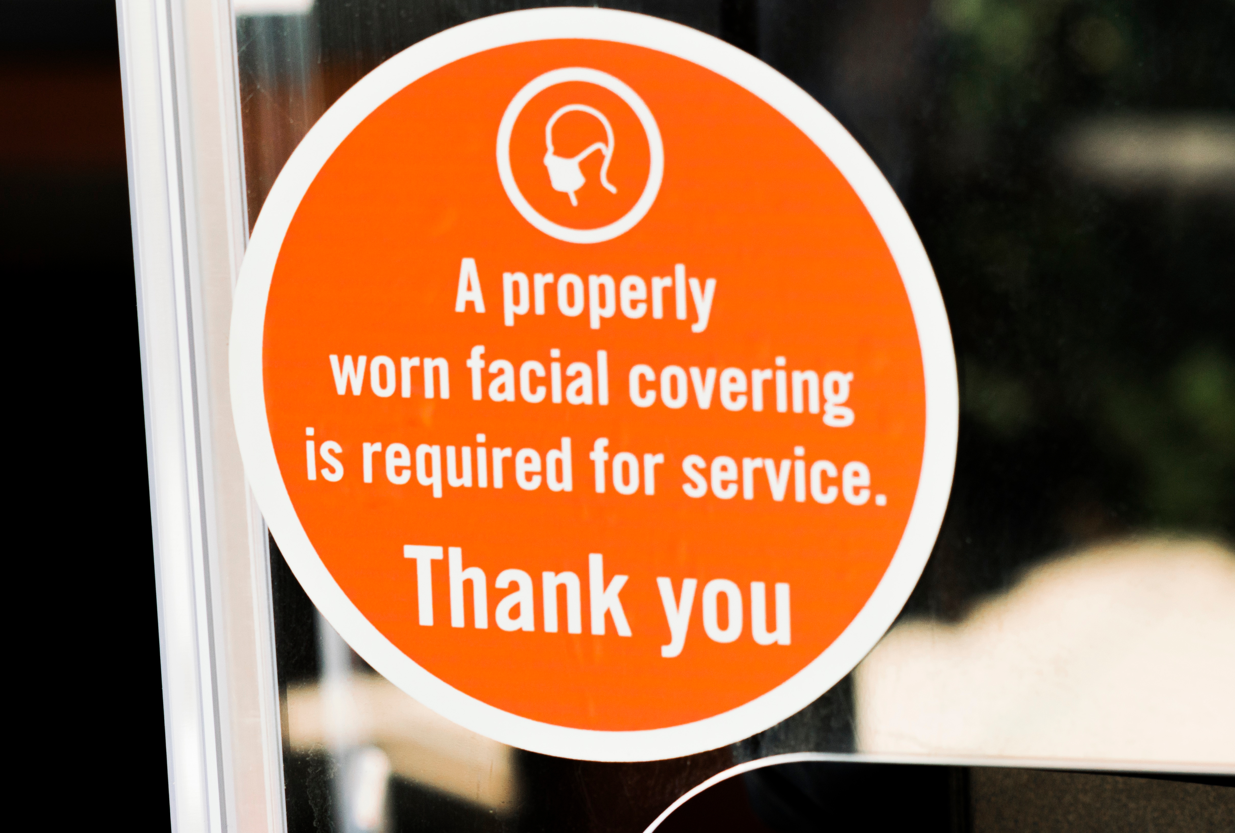 """An orange sign on a storefront window says """"A properly worn facial covering is required for service. Thank you"""""""