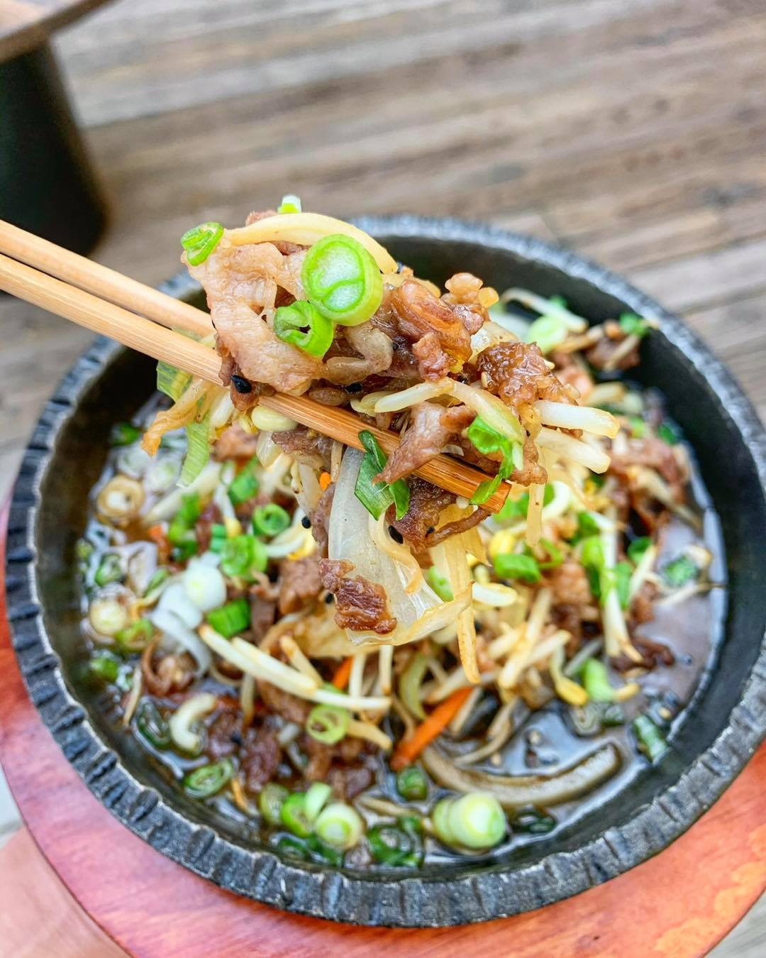 A Korean-style stone bowl filled with shaved meat, beat sprouts, sauce, green onions and more veggies. A hand holding chopsticks is lifting a bite out of the bowl.