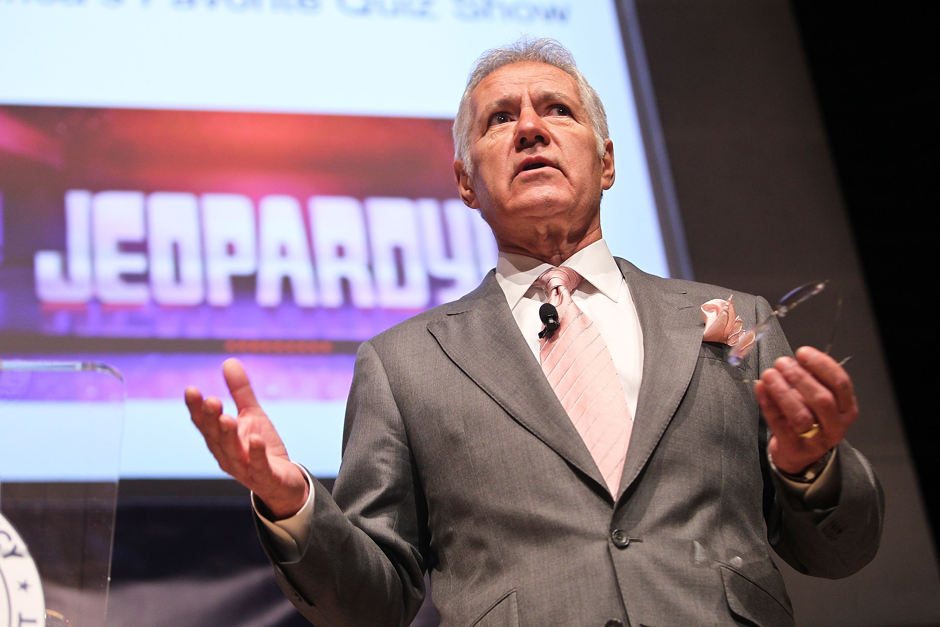 Alex Trebek standing on the set of the Jeopardy game show with the logo behind him on a screen.