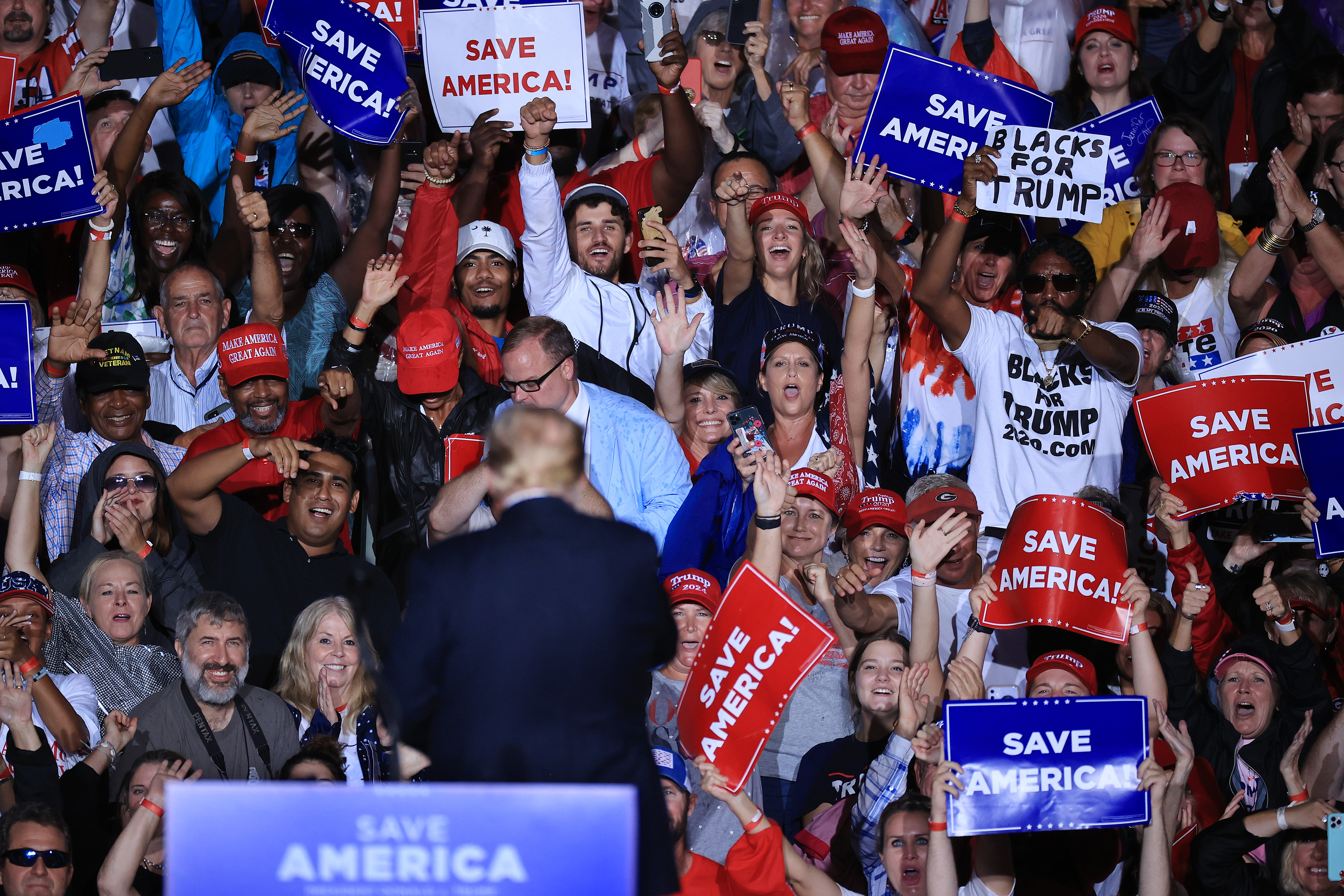 """Former President Donald Trump turns from the camera to face the crowd waving """"Save America"""" signs behind him at a rally."""