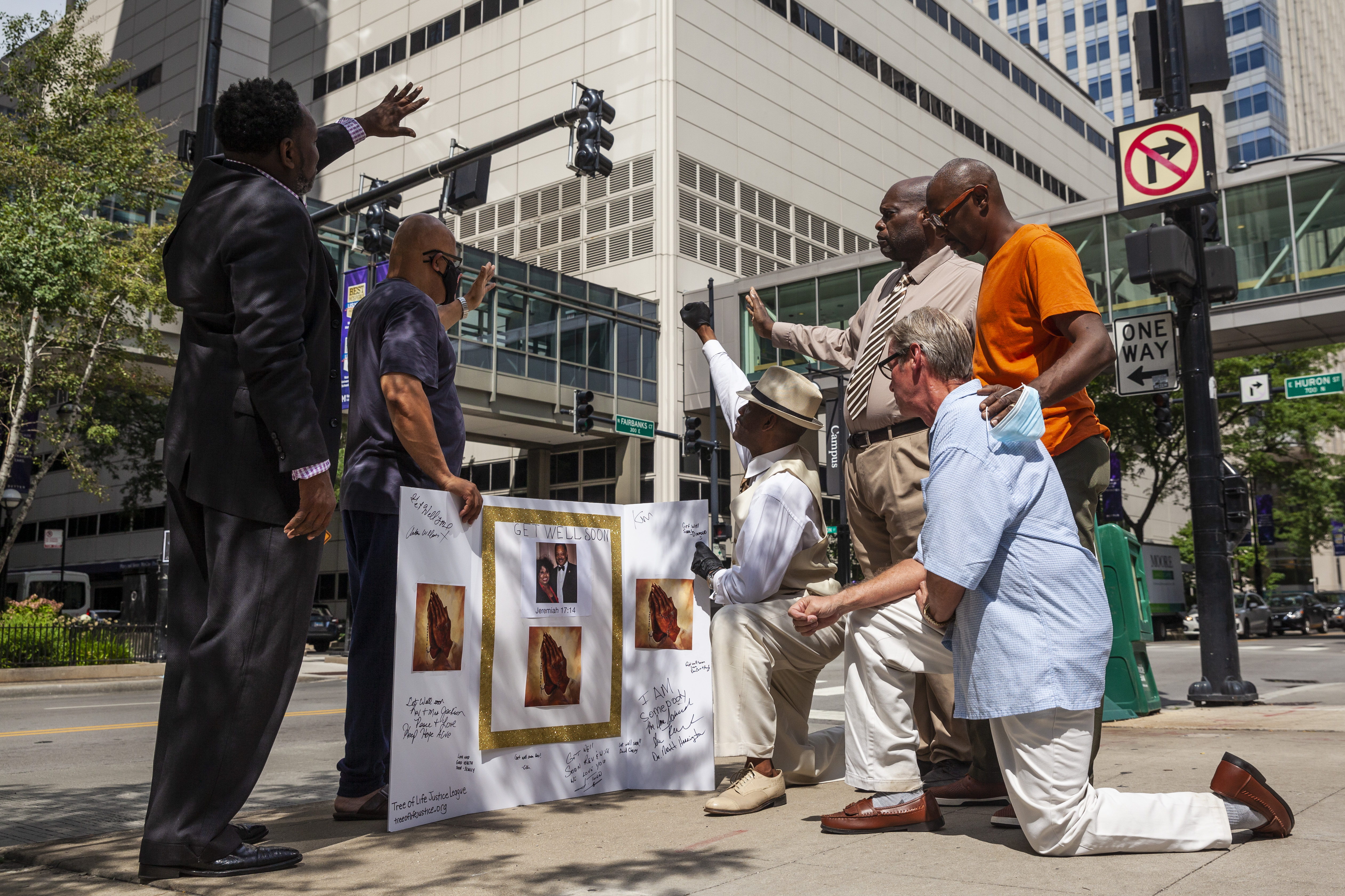 """Community activists and faith leaders get signatures for a """"get well soon"""" card for Rev. Jesse Jackson, 79, and his wife, Jacqueline, 77, before a prayer vigil and news conference outside Northwestern Memorial Hospital, Monday morning, Aug. 23, 2021. The Jacksons were admitted Saturday to Northwestern after testing positive for COVID-19."""