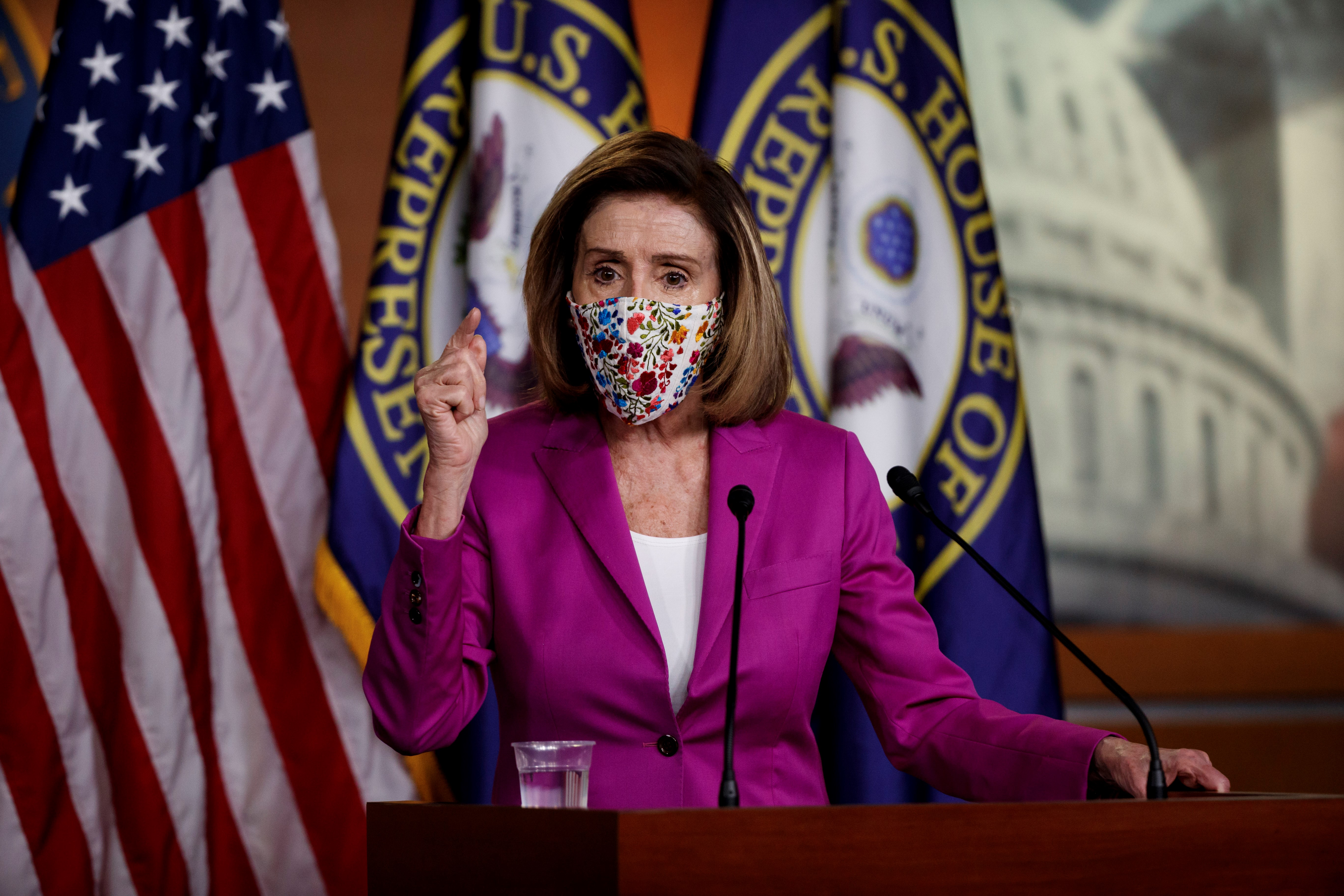 Pelosi, in a dark pink suit, white blouse, and colorful cloth mask, speaks emphatically into a microphone in front of the US and House of Representatives flags.