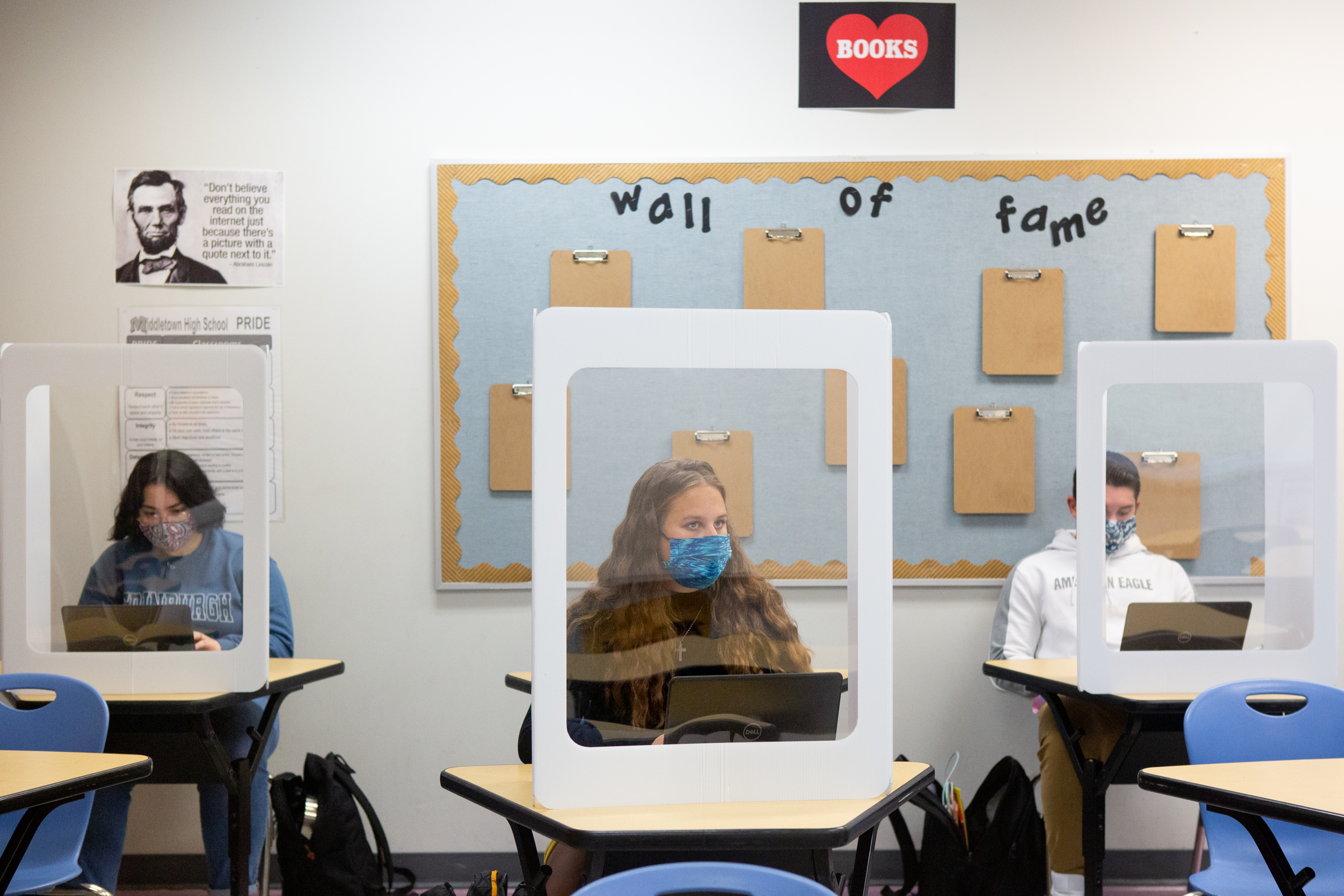 Student wearing a face masks seated behind desk shields.