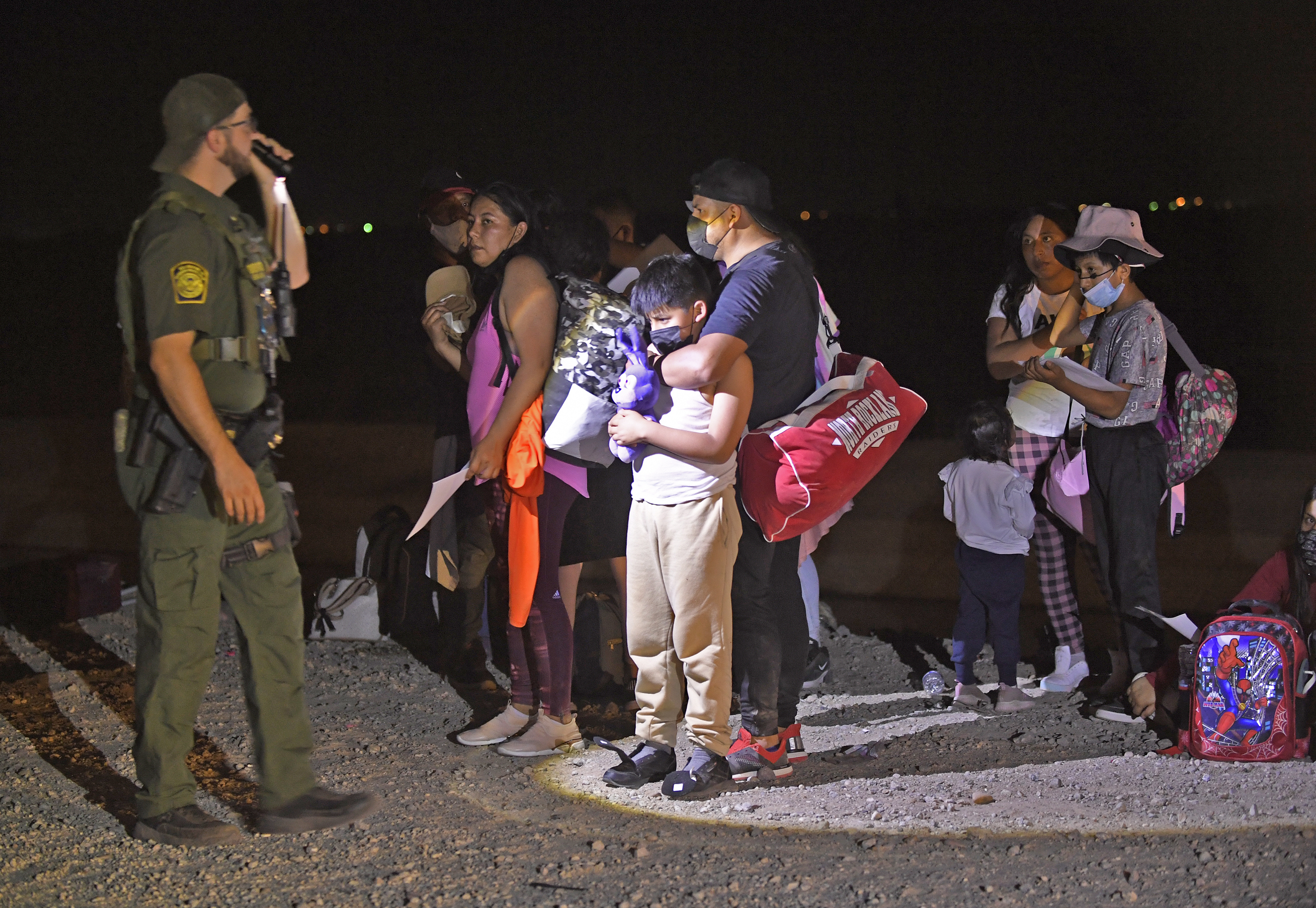 A border agent shines a flashlight on a group of migrants.