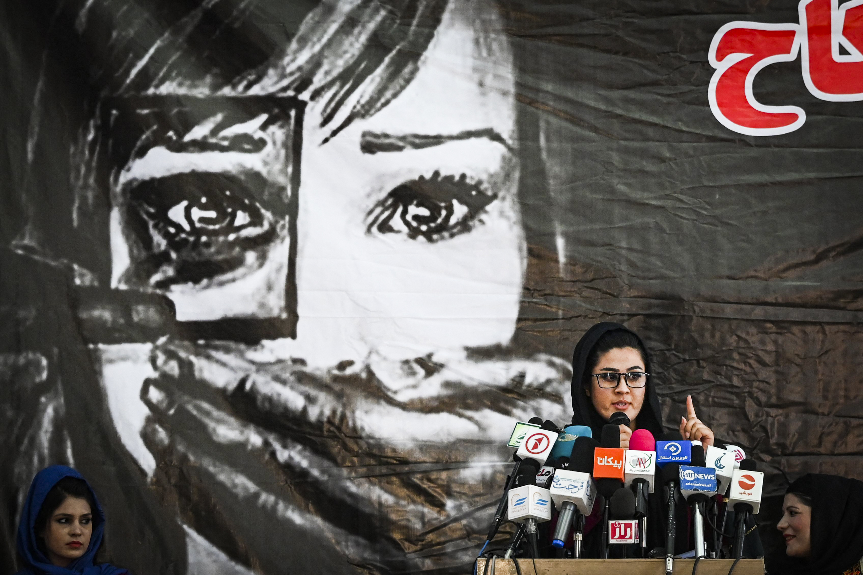 An Afghan woman onstage in Kabul speaks into a cluster of microphones in front of a large illustration of a woman with a hand covering her mouth.