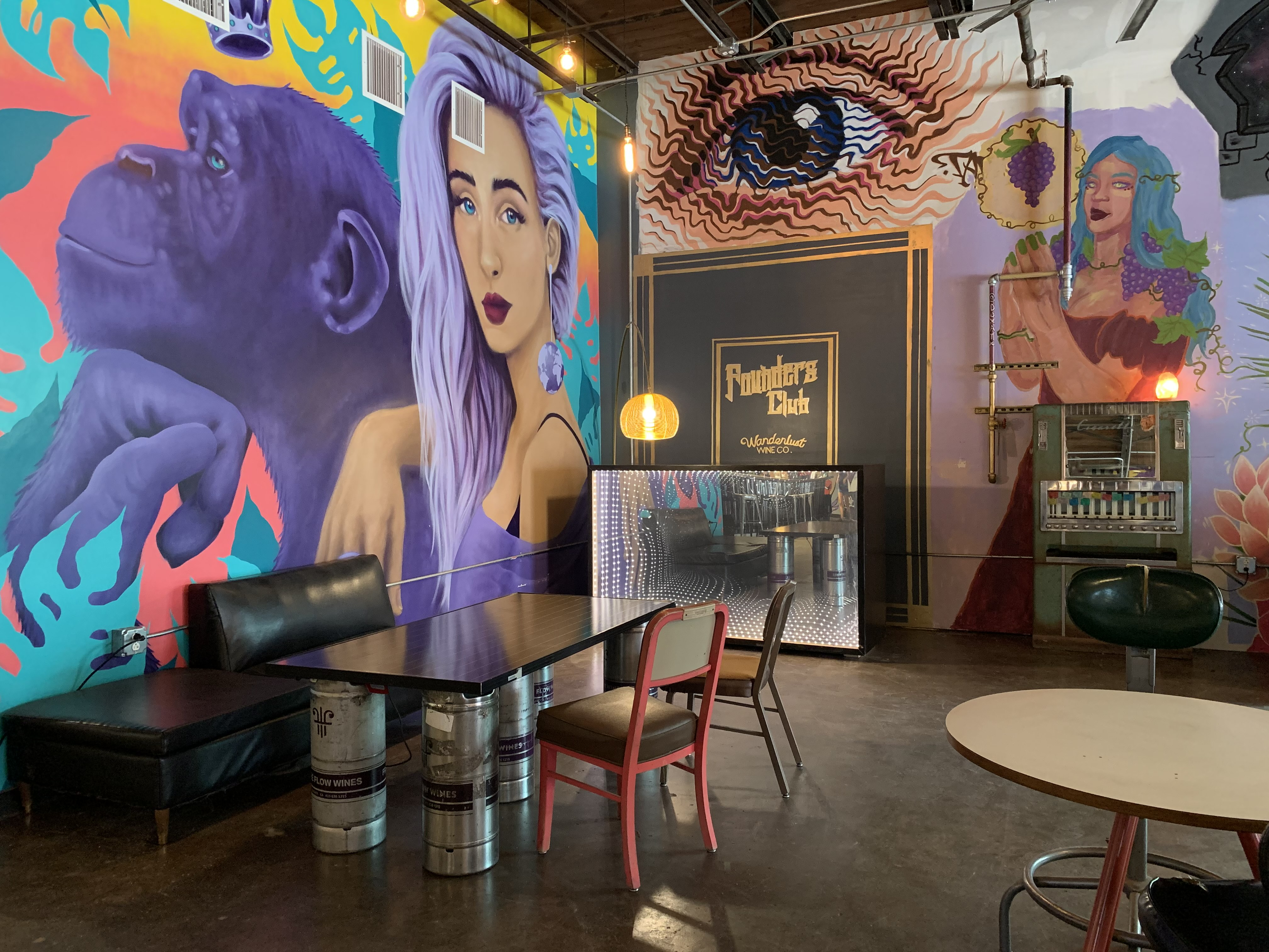 A table with a bunch of brightly colored murals (a woman, a chimpanzee, an eye, etc.)