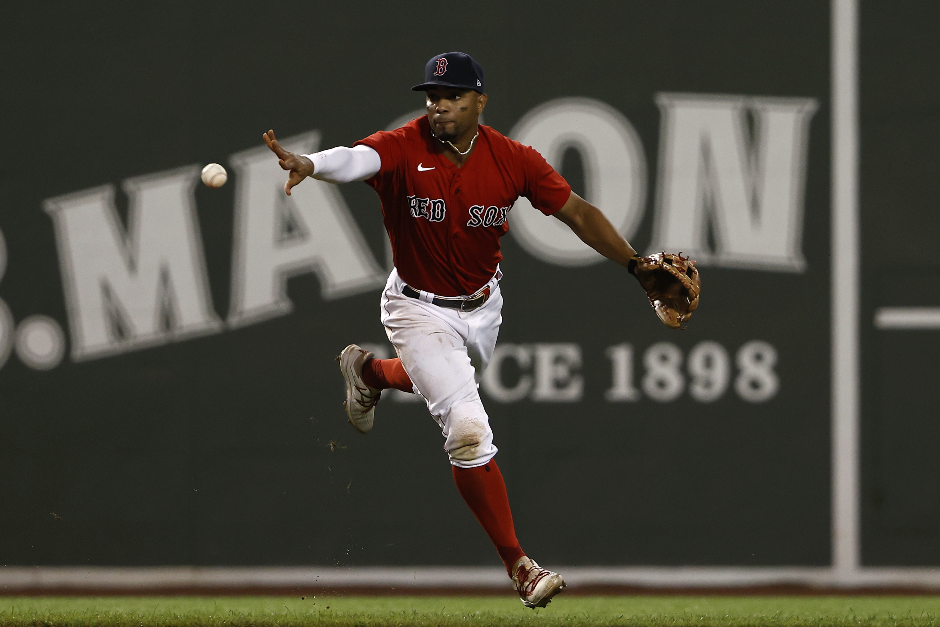 Xander Bogaerts #2 of the Boston Red Sox shovels the ball to second base for a force out during the sixth inning against the Texas Rangers at Fenway Park on August 21, 2021 in Boston, Massachusetts.