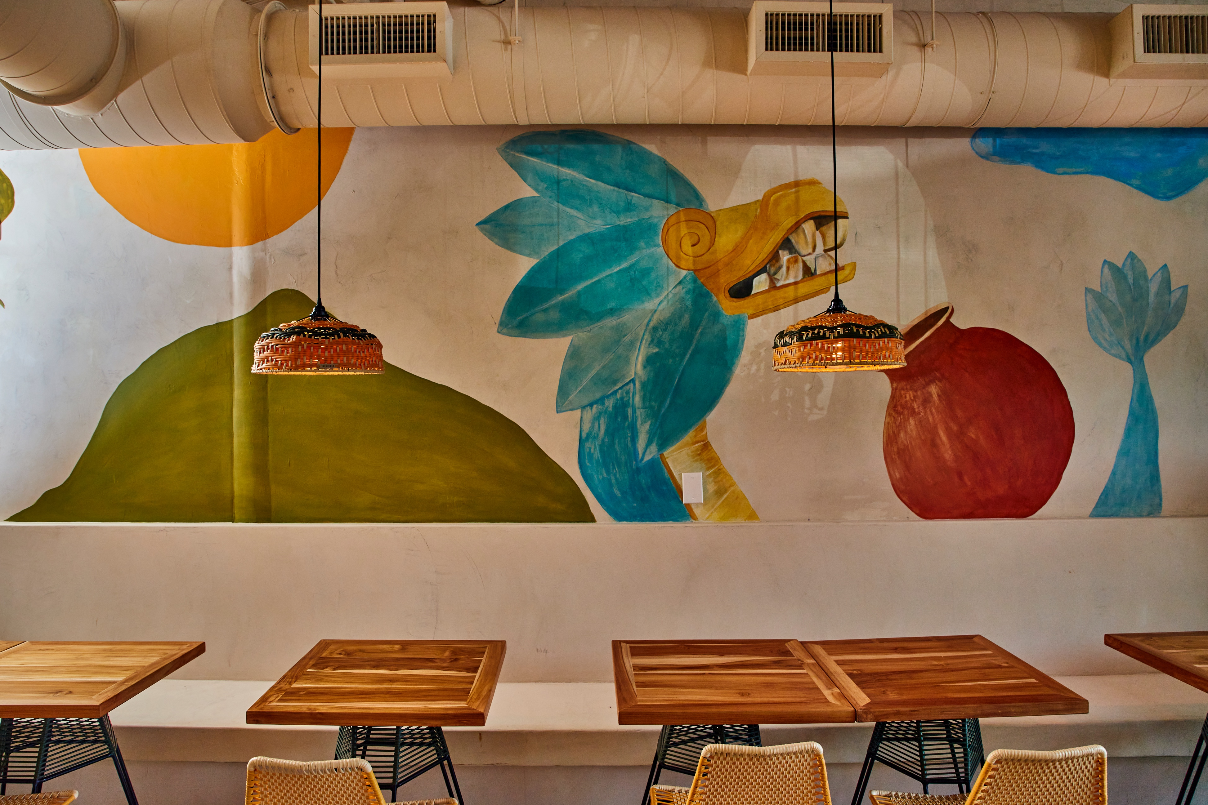 dining room with bright color mural and chairs in the foreground