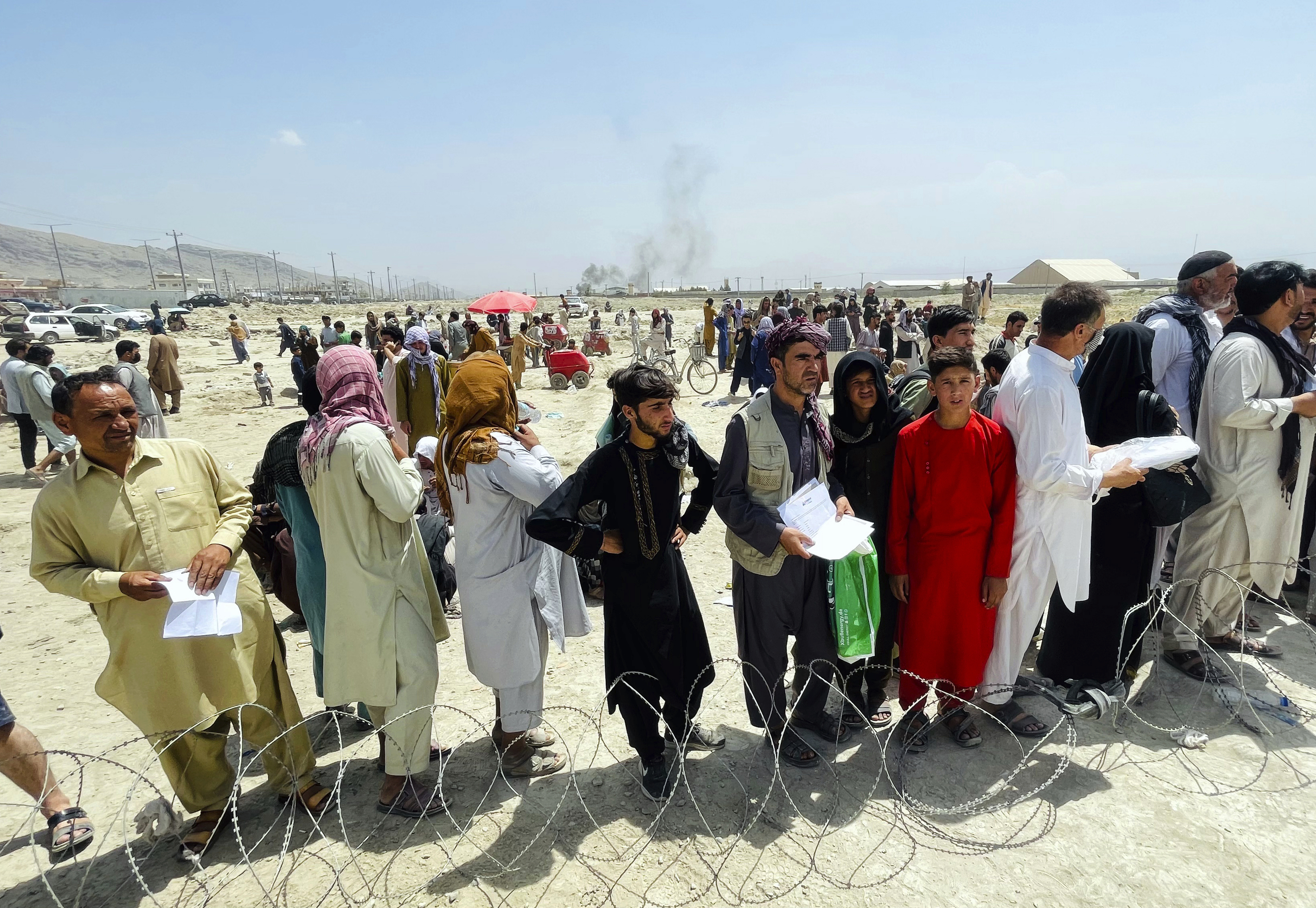 Hundreds of Afghans gather outside the airport in Kabul, Afghanistan, hoping to leave their country.