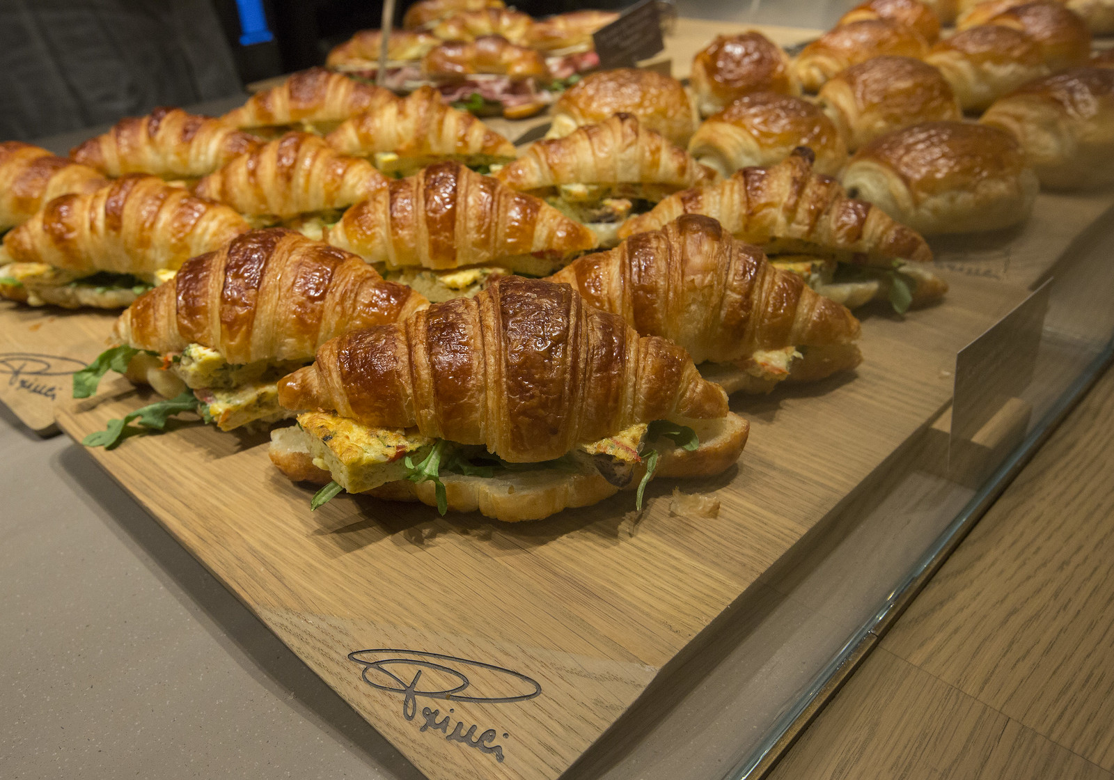 A croissant sandwich on a wooden platter.