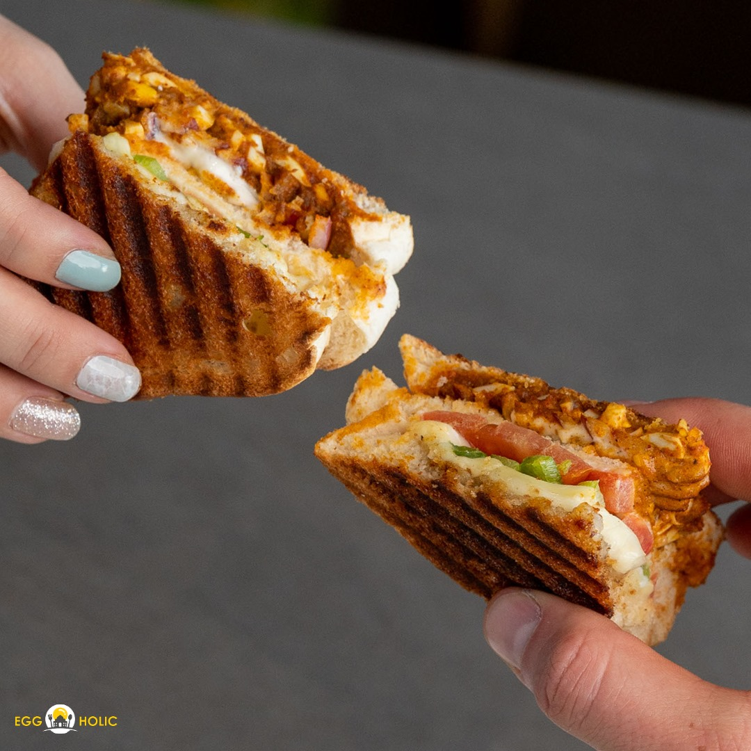 two different hands holding slices of a toasted egg sandwich