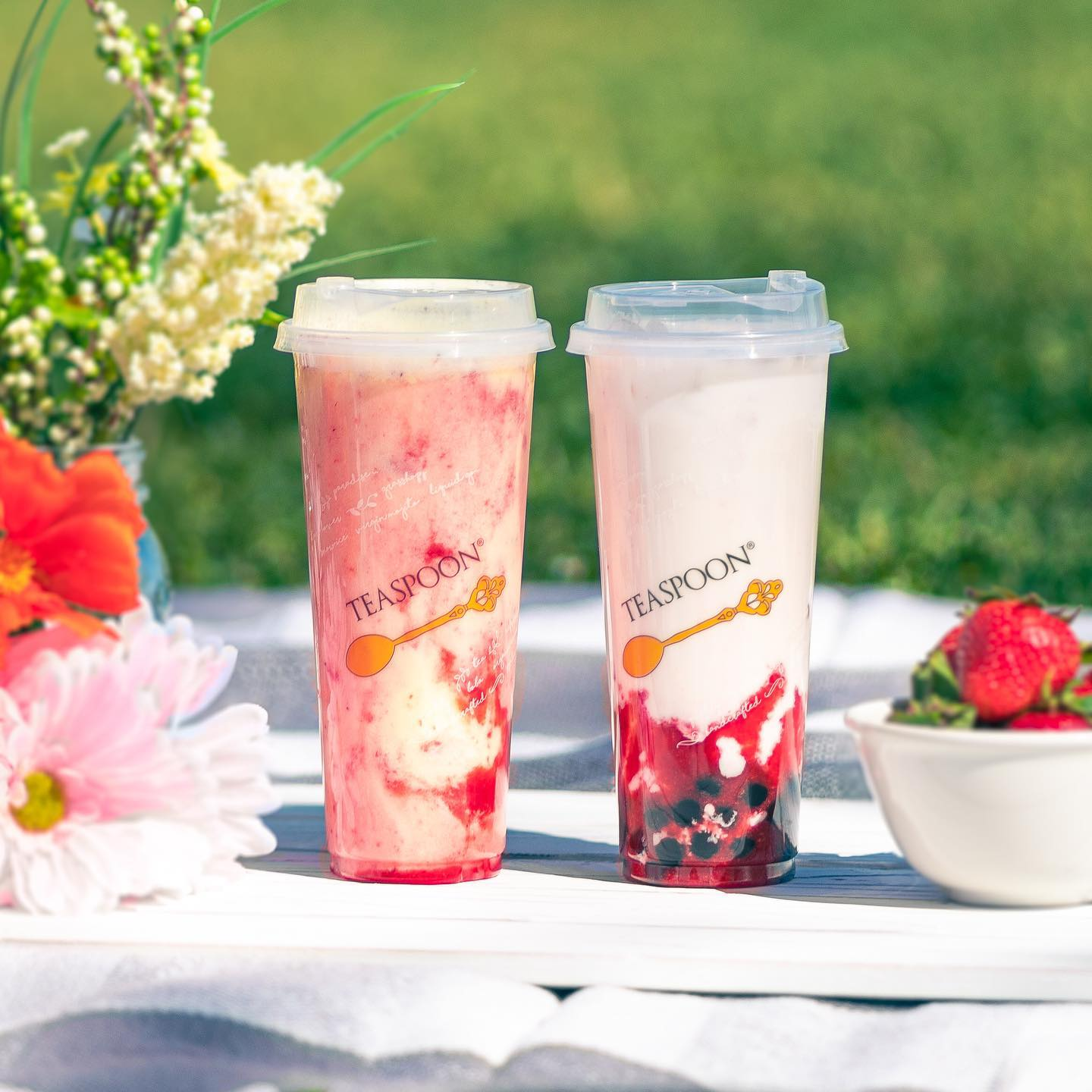 Silky strawberry and strawberry colada boba teas in clear glasses with flowers on one side and strawberries on the other