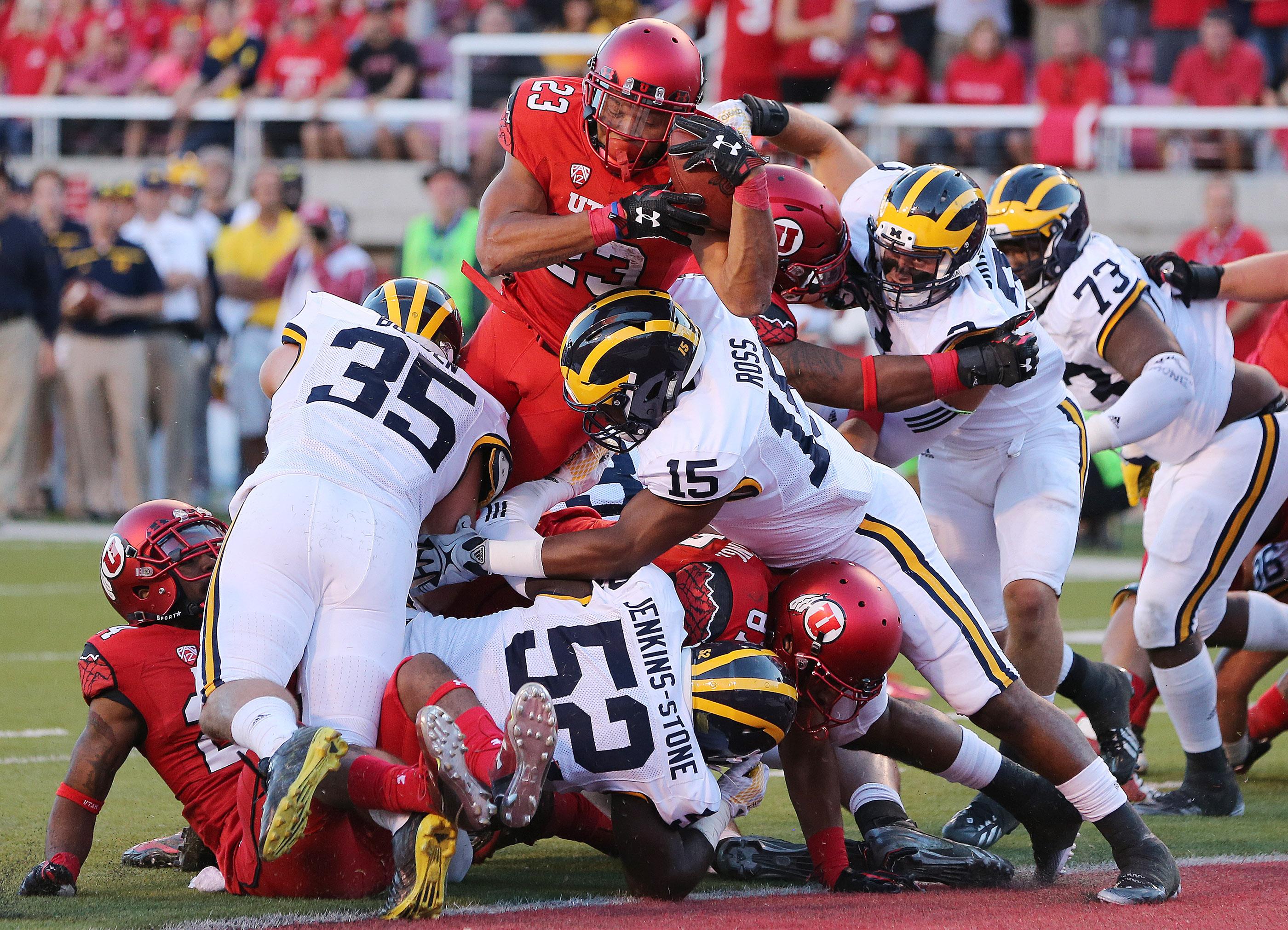 Utah Utes running back Devontae Booker (23) dives over Michigan for a touchdown.