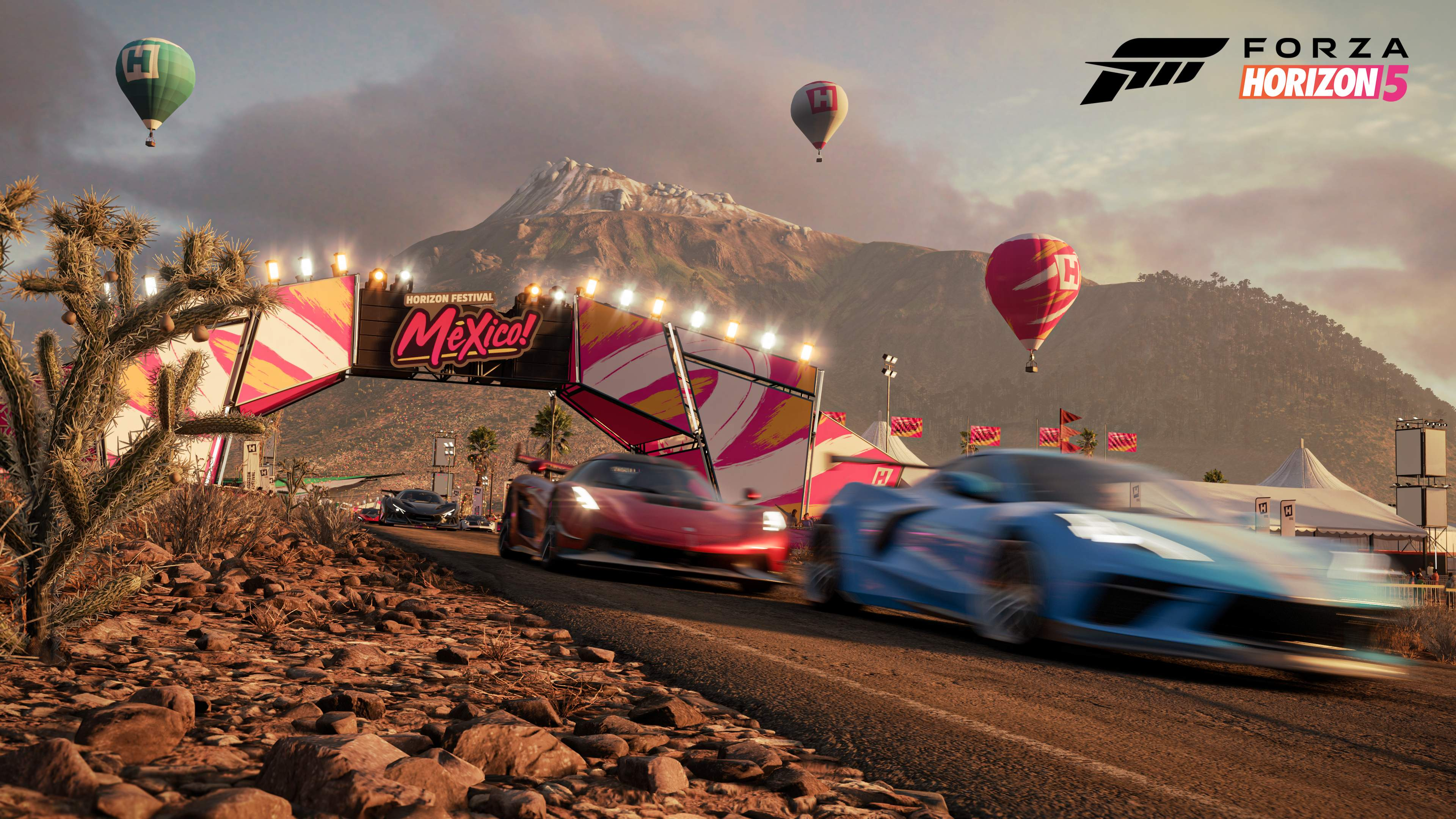Cars race down a highway as festival lights and hot air balloons hang in the distance behind them