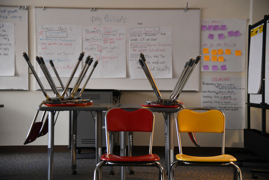 Two empty chairs sit in an empty classroom.