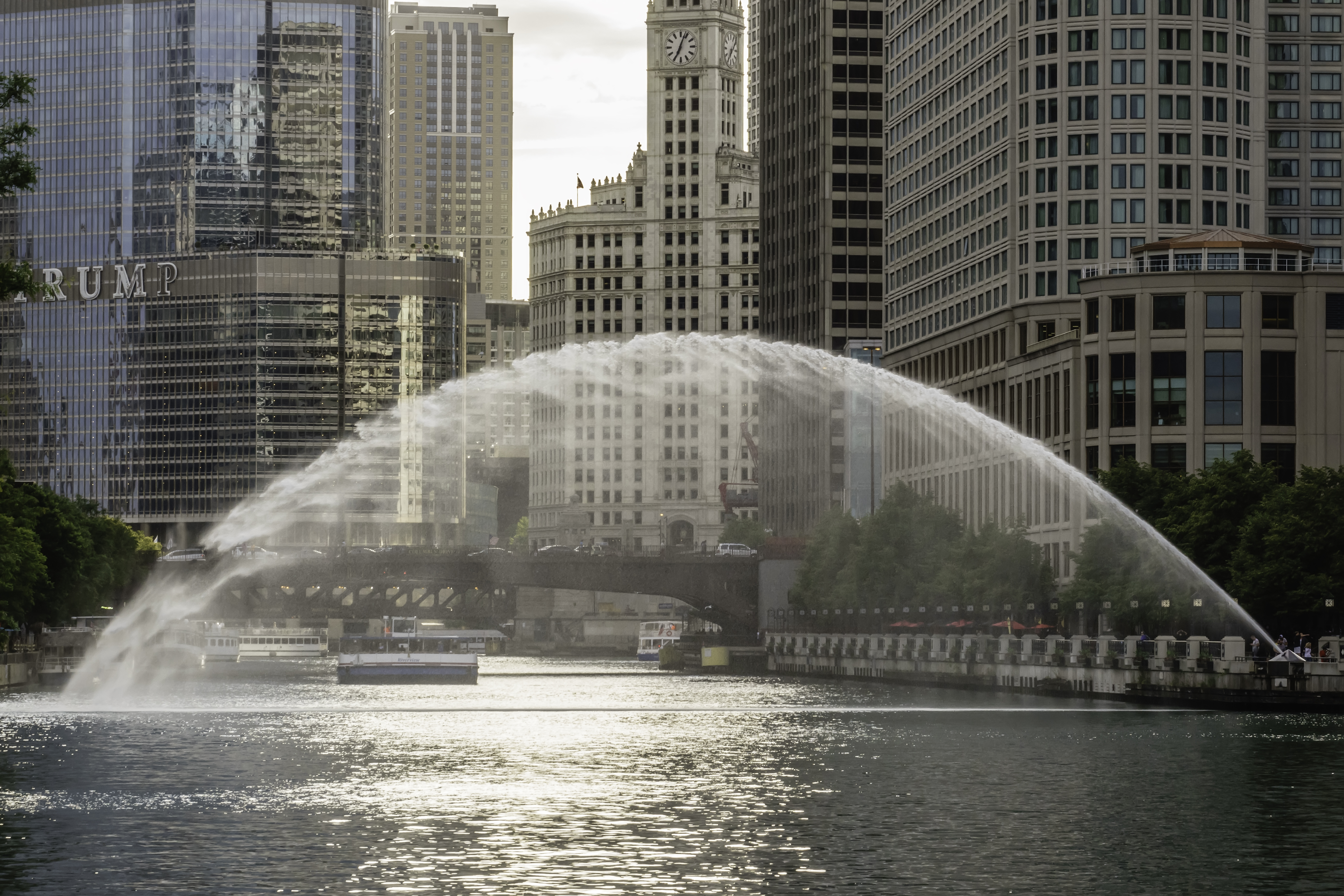 A view down the Chicago River with a fountain spraying from bank to bank.