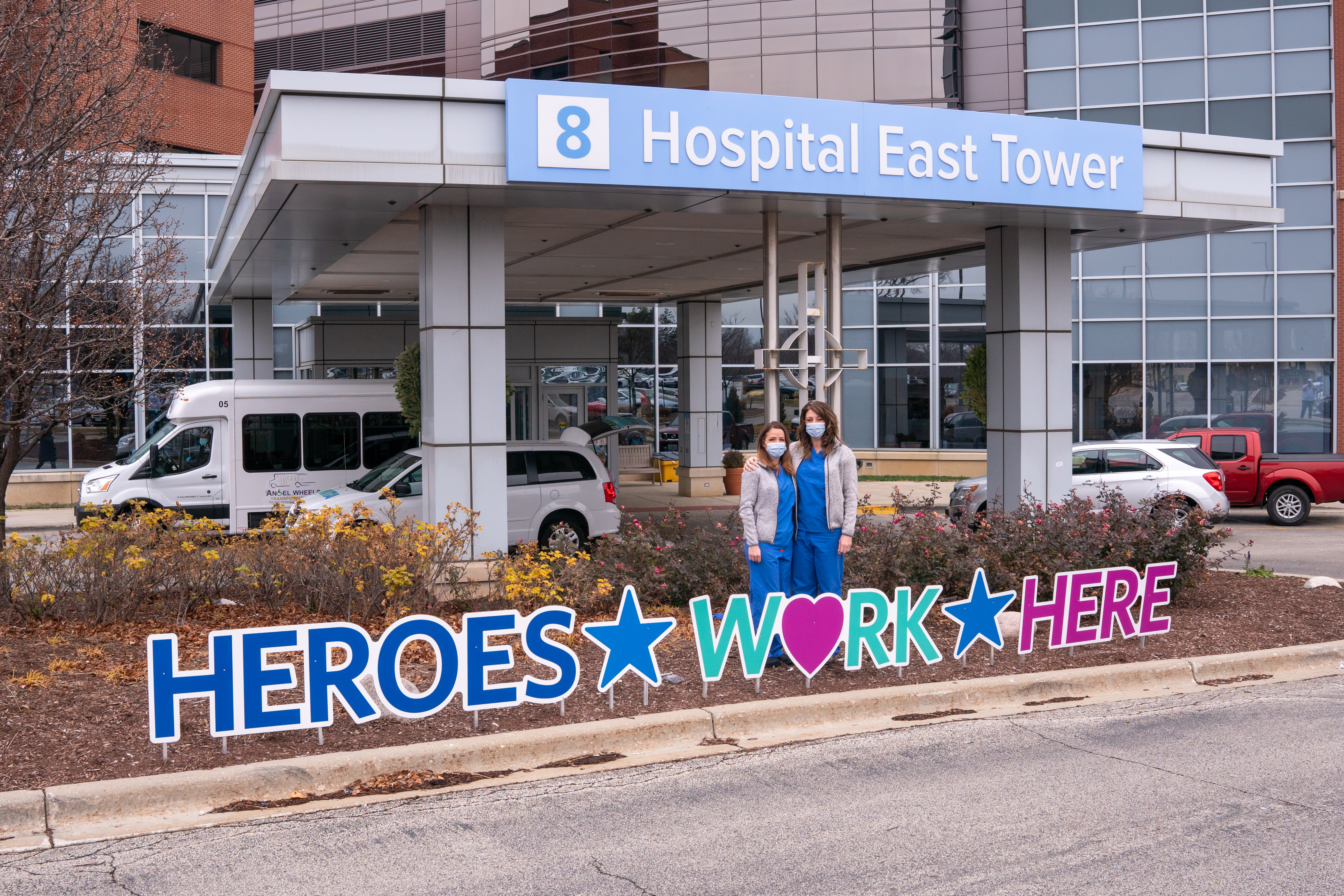 """Critical care nurses Kirsten Shea, RN (L) and Kathryn Lullo, RN (R) pose for a portrait in front of signs saying """"Heroes Work Here,"""" outside AMITA Health Alexian Brothers Medical Center Elk Grove Village in December 2020."""