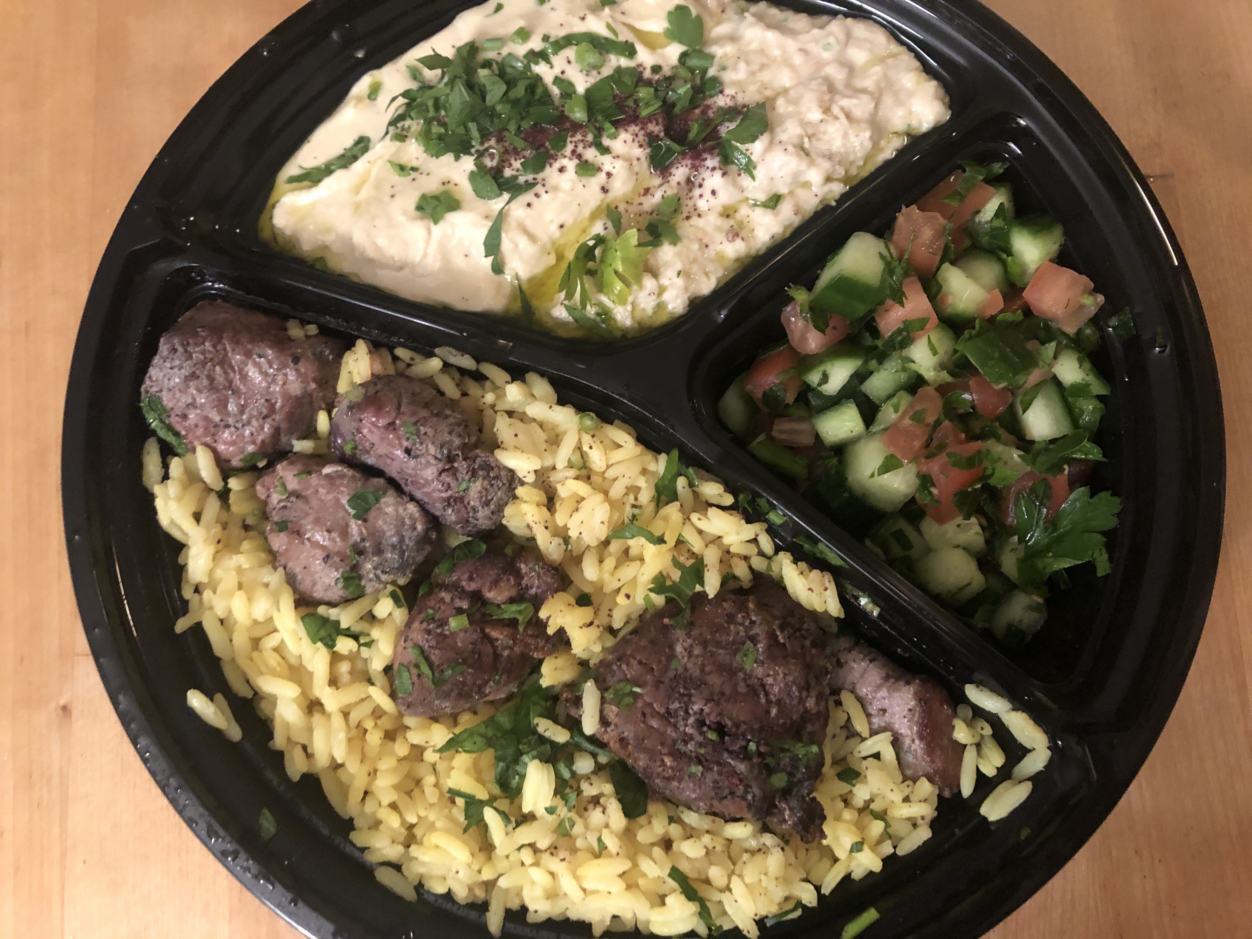 An overhead photograph of a takeout container with hummus, cucumber salad, rice, and grilled meat