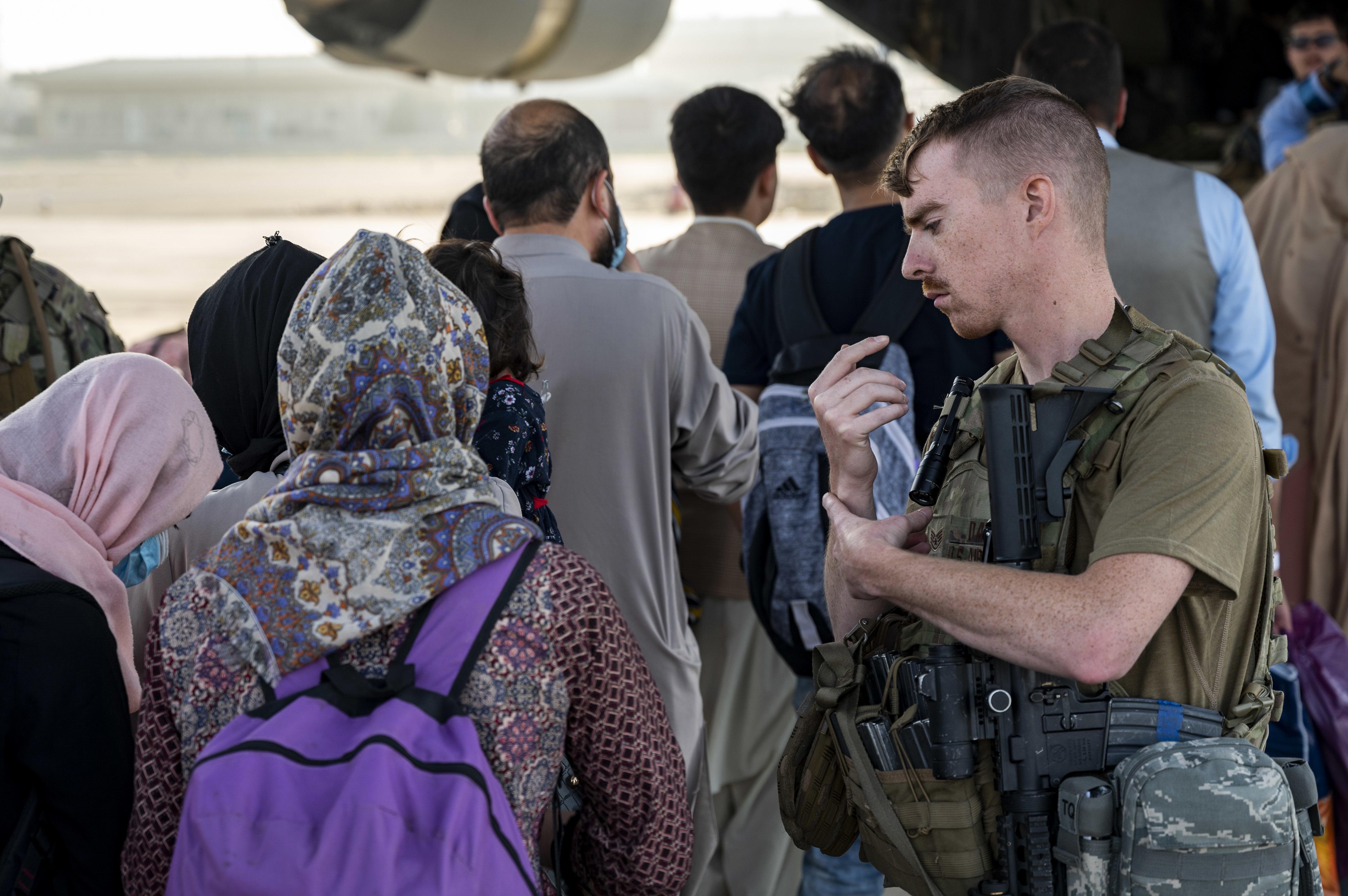 A U.S. airman helps evacuees board a military airplane in Afghanistan.