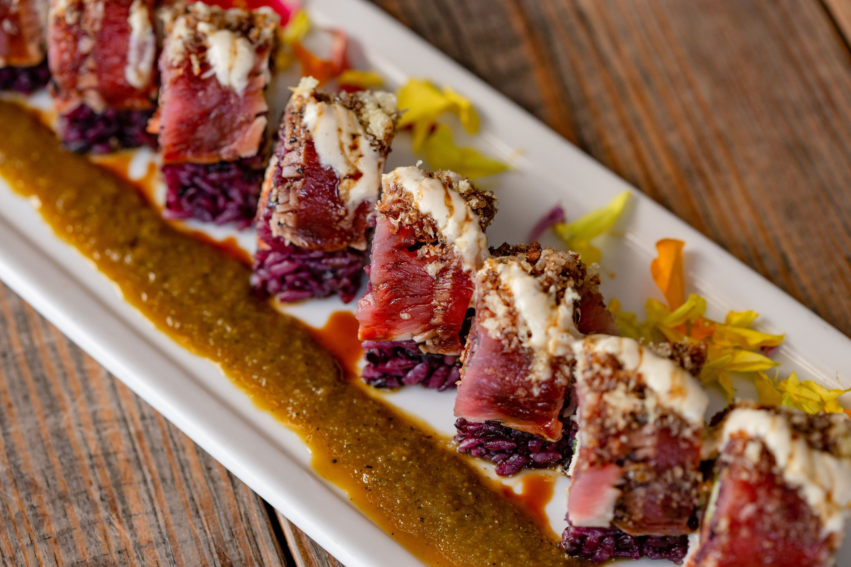 a sushi roll with raw tuna, black rice, and some kind of sauce neatly arranged in slices on a rectangular white plate