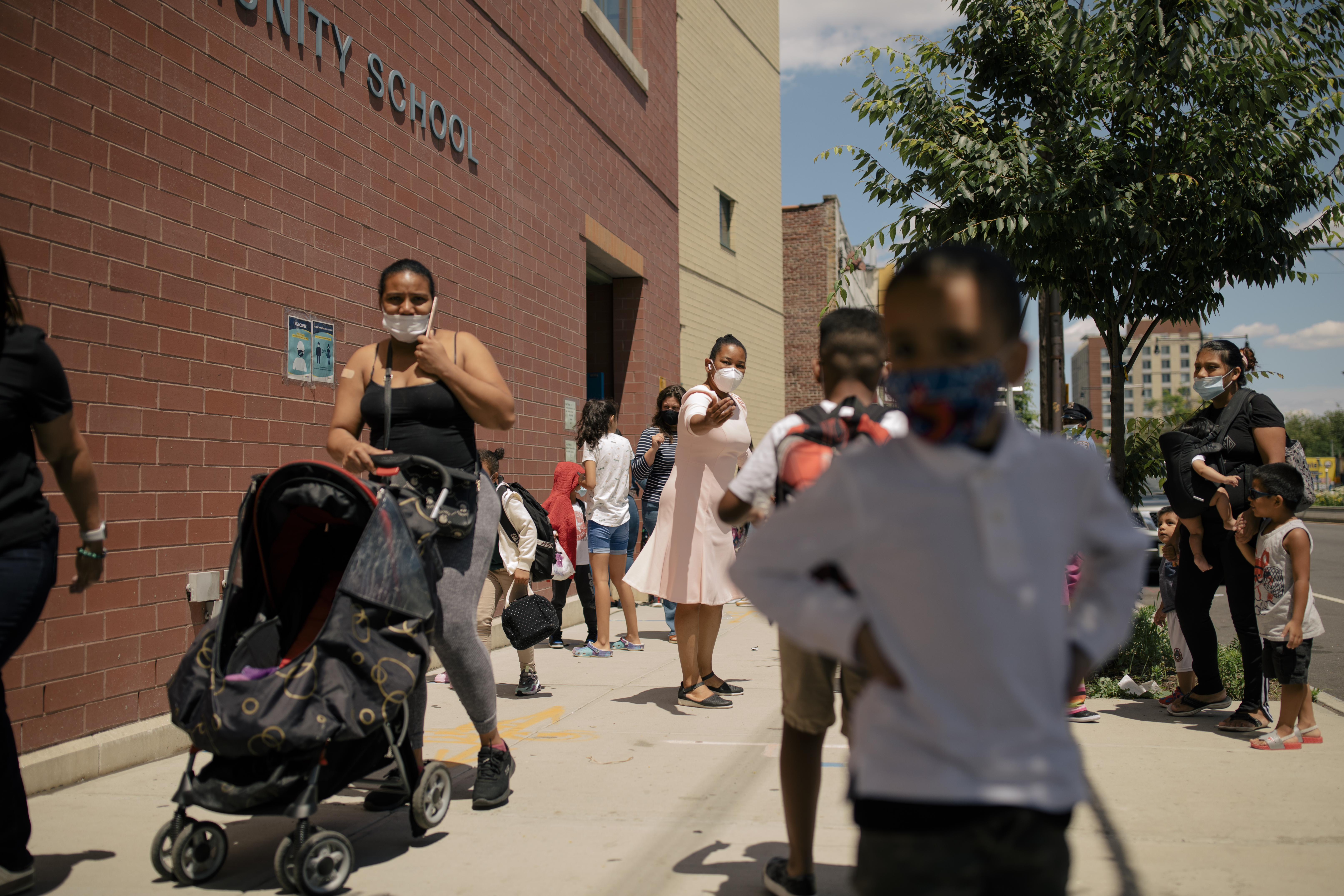 Students walk outside a school in Brooklyn. The school is brick, and a young student in a white shirt is in the foreground.