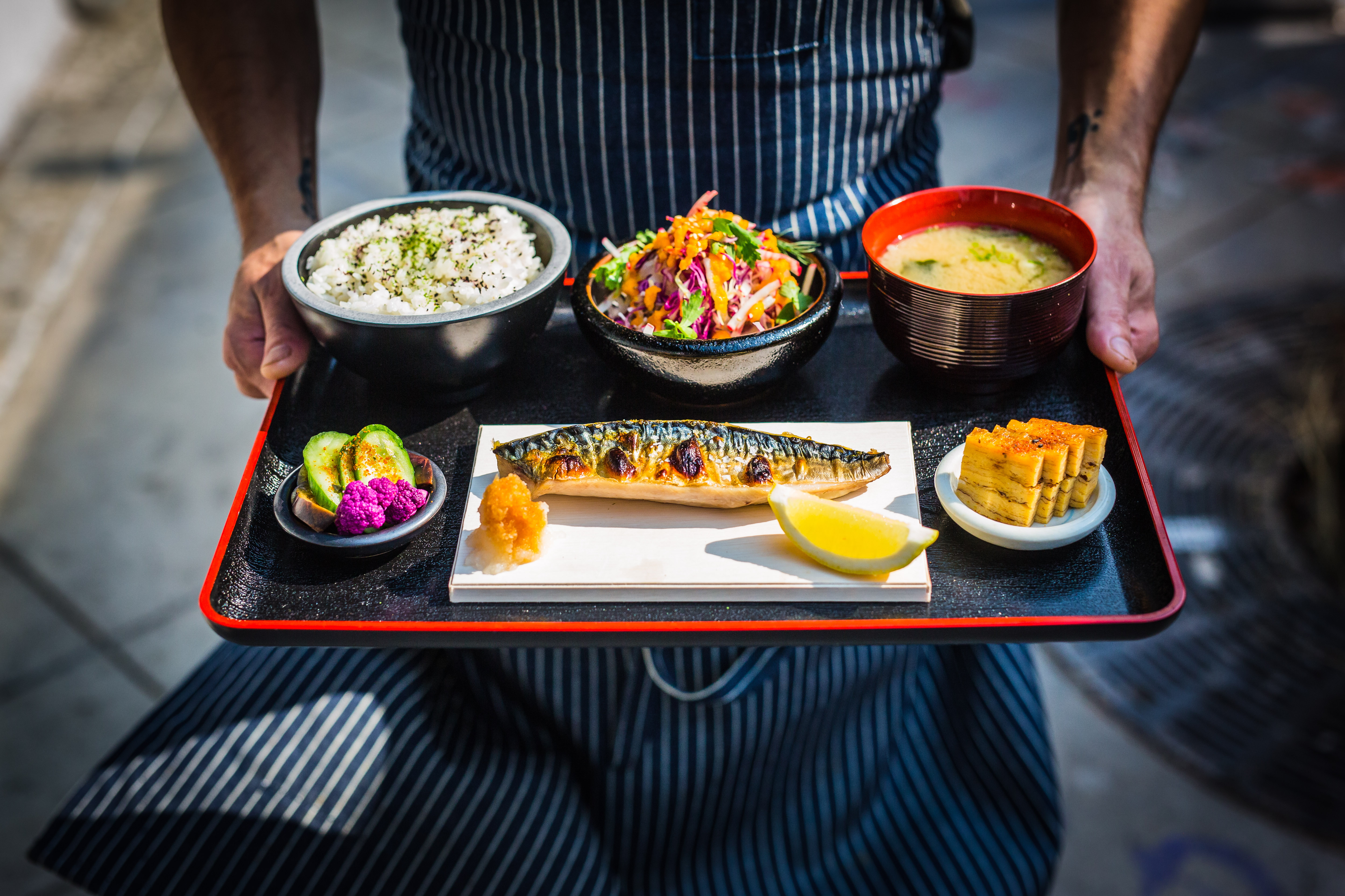 An overhead shot of a tray of Japanese food, including fried fish, held in hands.