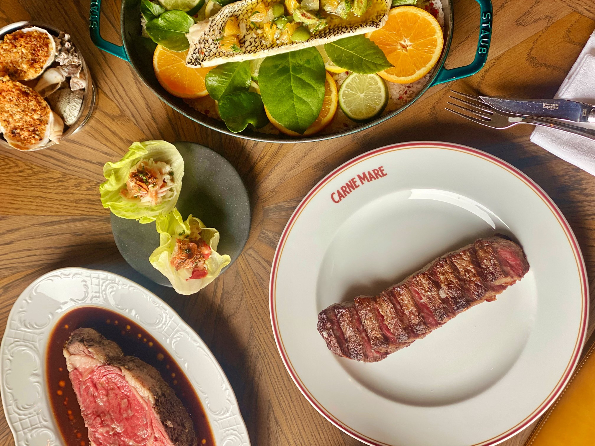 An overhead shot of a New York strip loin on a white plate; that steak sits adjacent a fish dish underneath oranges, warm oysters, and a prime rib with jus