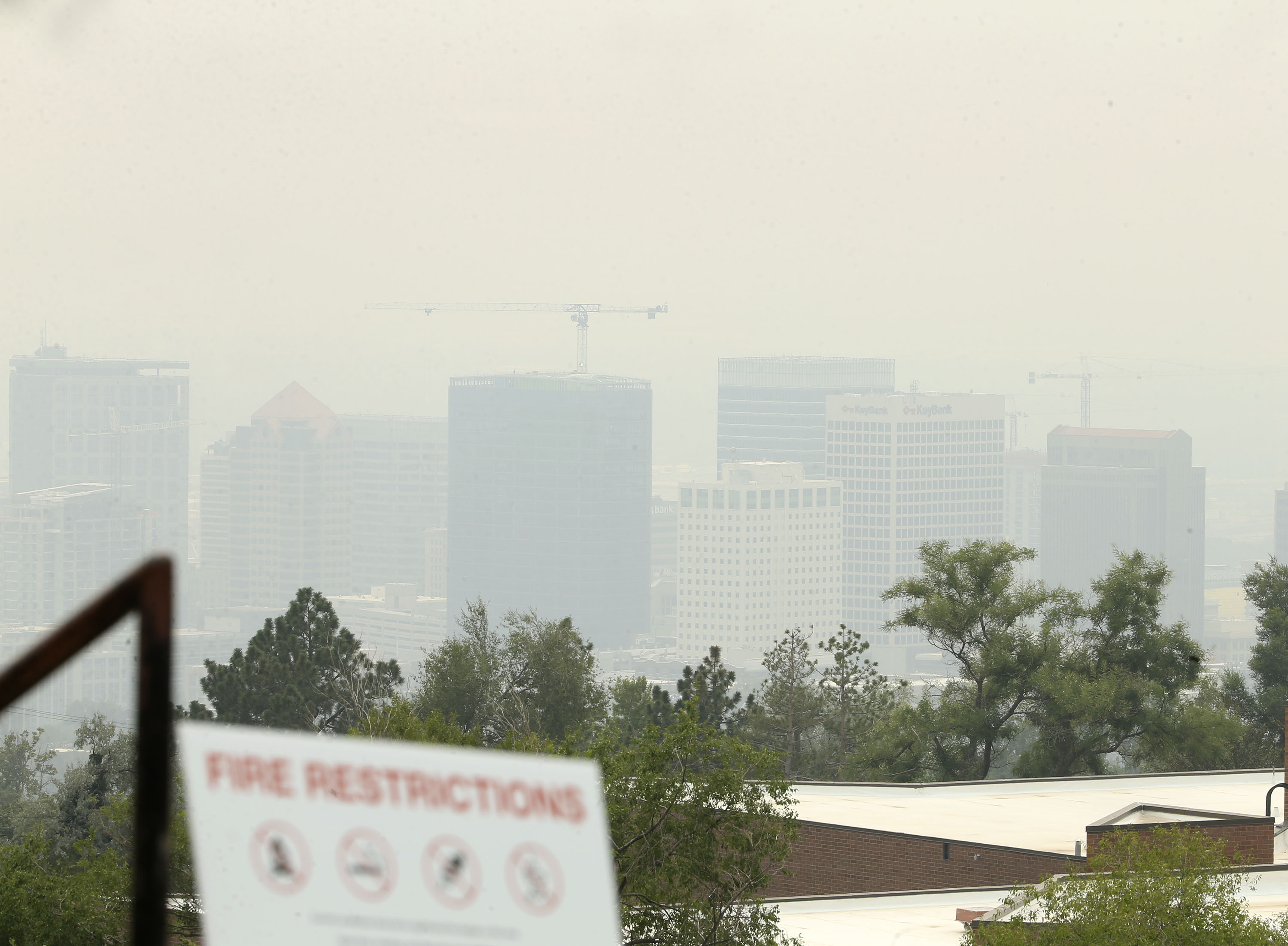 A fire restrictions warning sign is posted in Salt Lake City, obscured by smoke from the California and Oregon wildfires.