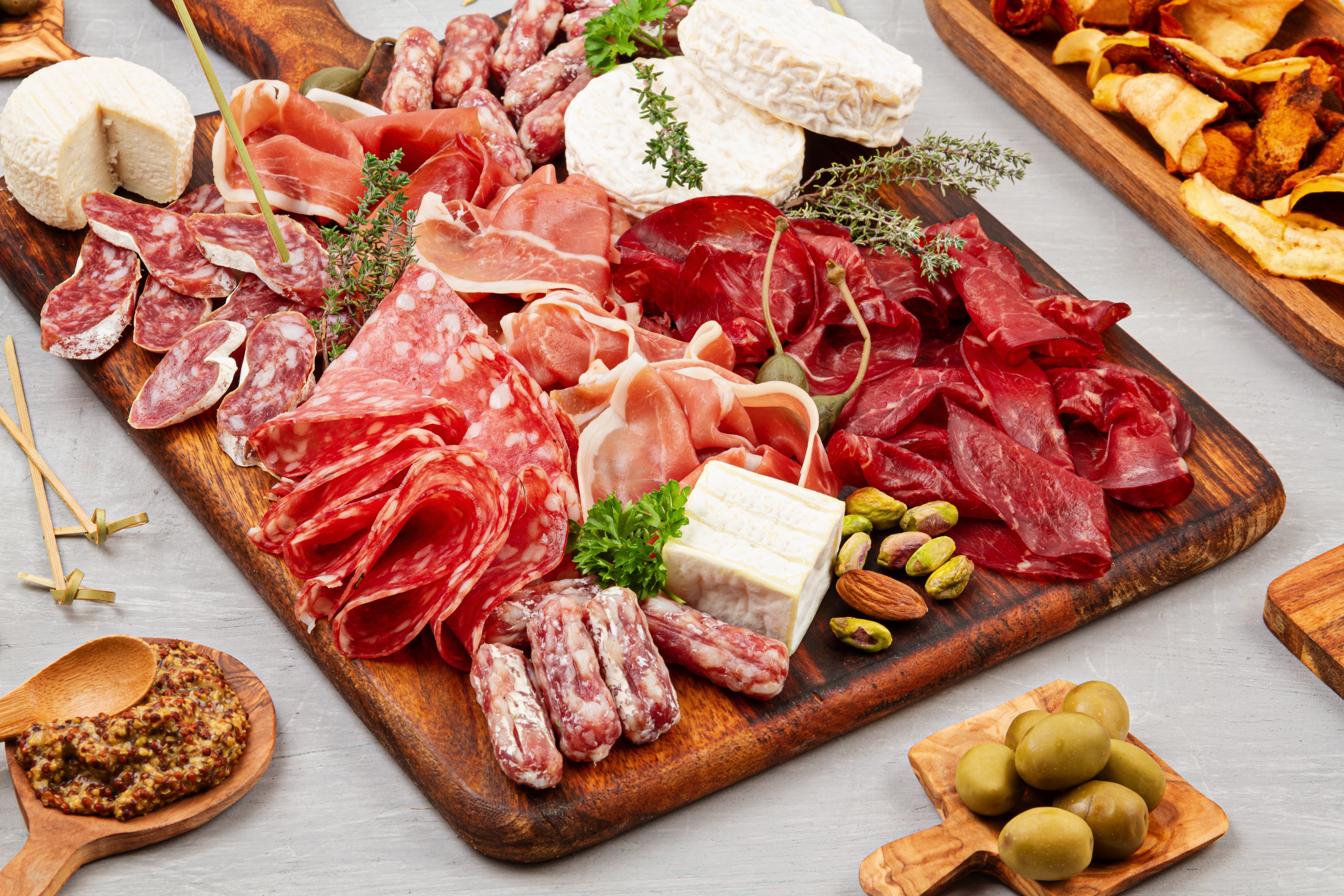 An angled overhead photo of a charcuterie board with various meats and cheeses.
