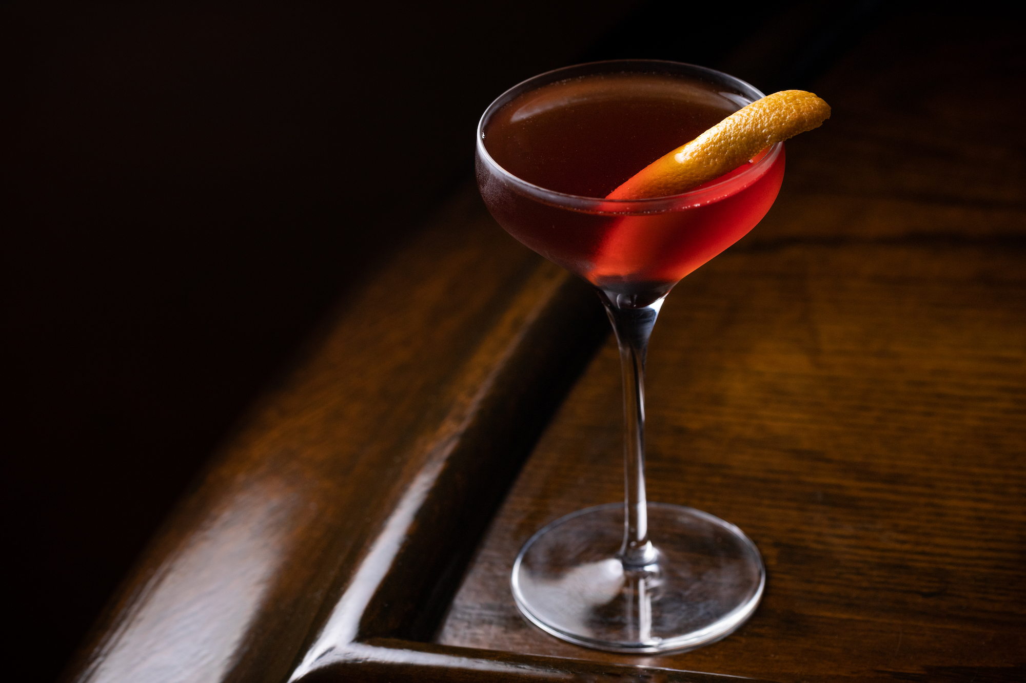 A coupe glass with red liquid and peel of citrus at the corner of a dark bar.