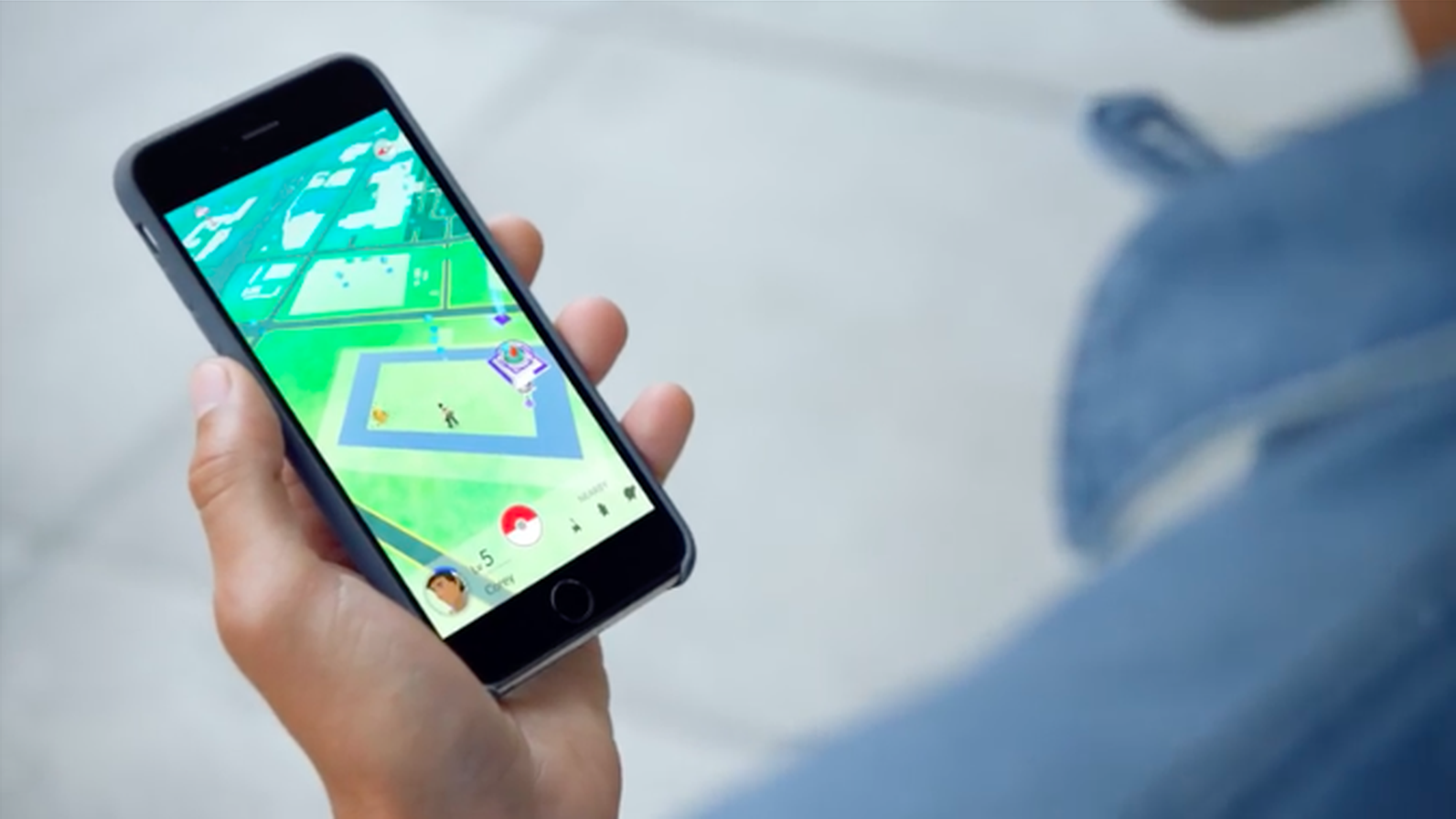 Man holding phone playing Pokémon Go