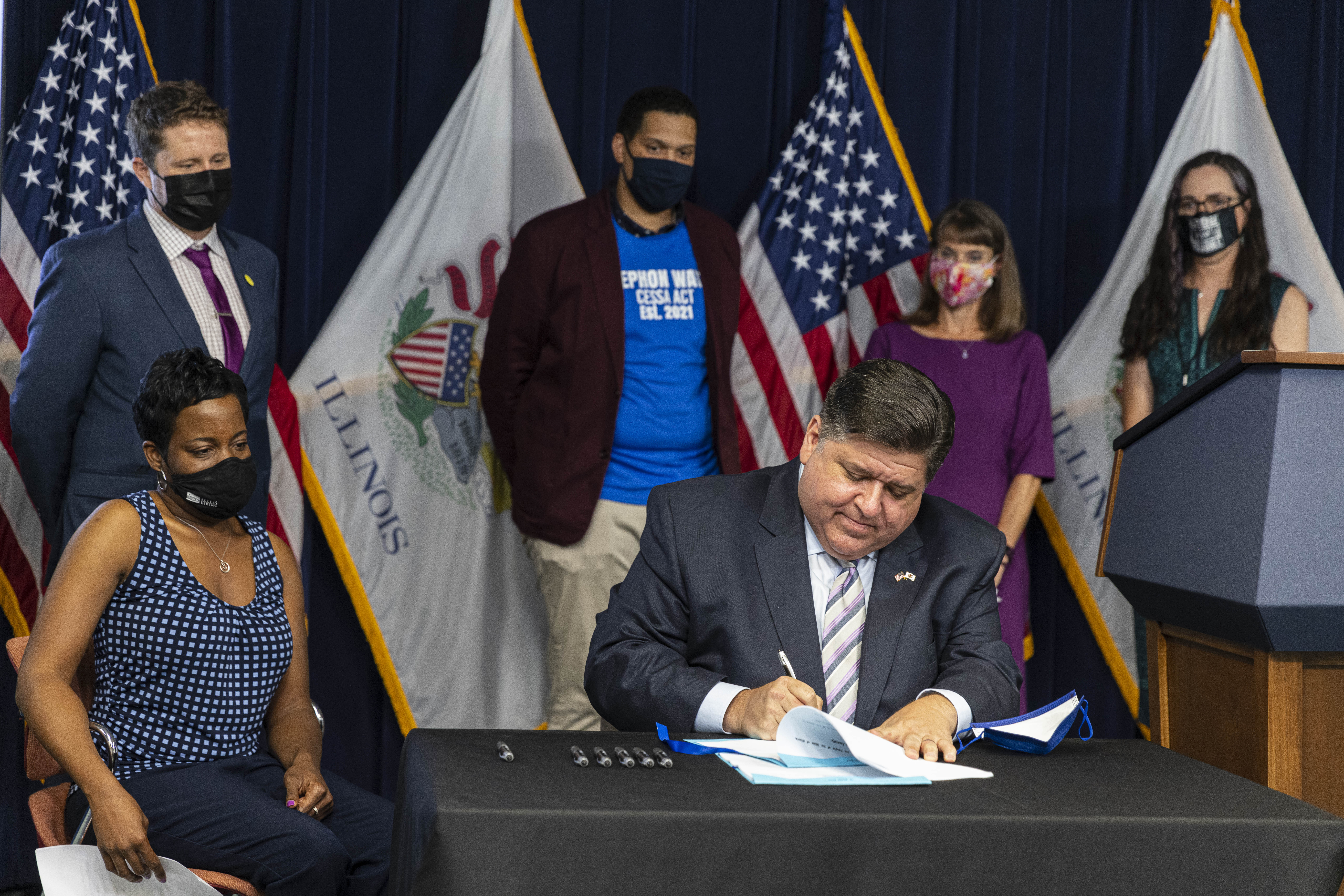 Gov. J.B. Pritzker signs bills to expand access to mental health care in Illinois at the Thompson Center on Wednesday.