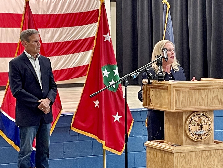 Gov. Bill Lee listens at Health Commissioner Dr. Lisa Piercey talks at a wooden podium.