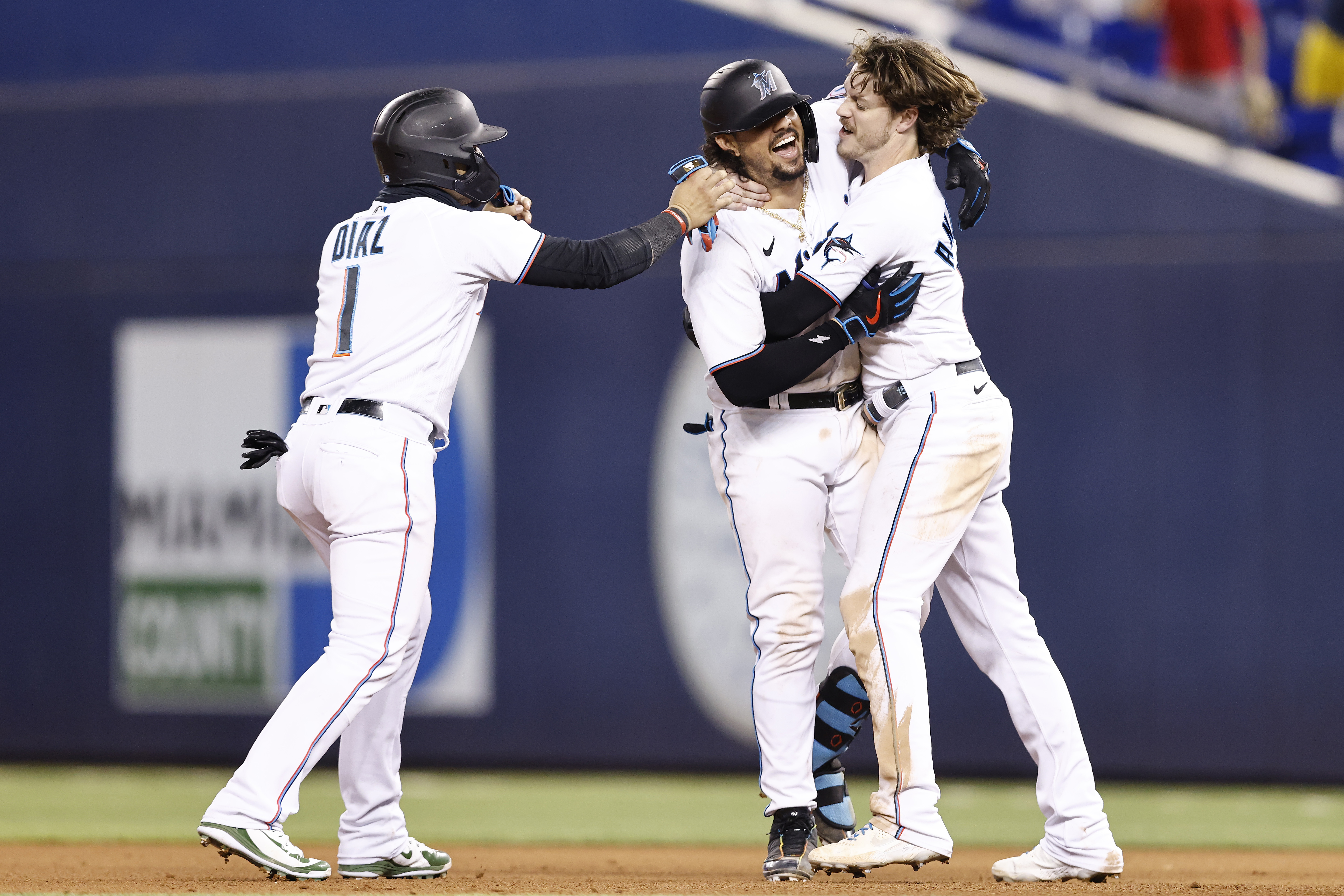 Jorge Alfaro #38 of the Miami Marlins celebrates with Brian Anderson #15 and Isan Diaz #1 after hitting a walk-off RBI single during the tenth inning against the Washington Nationals at loanDepot park