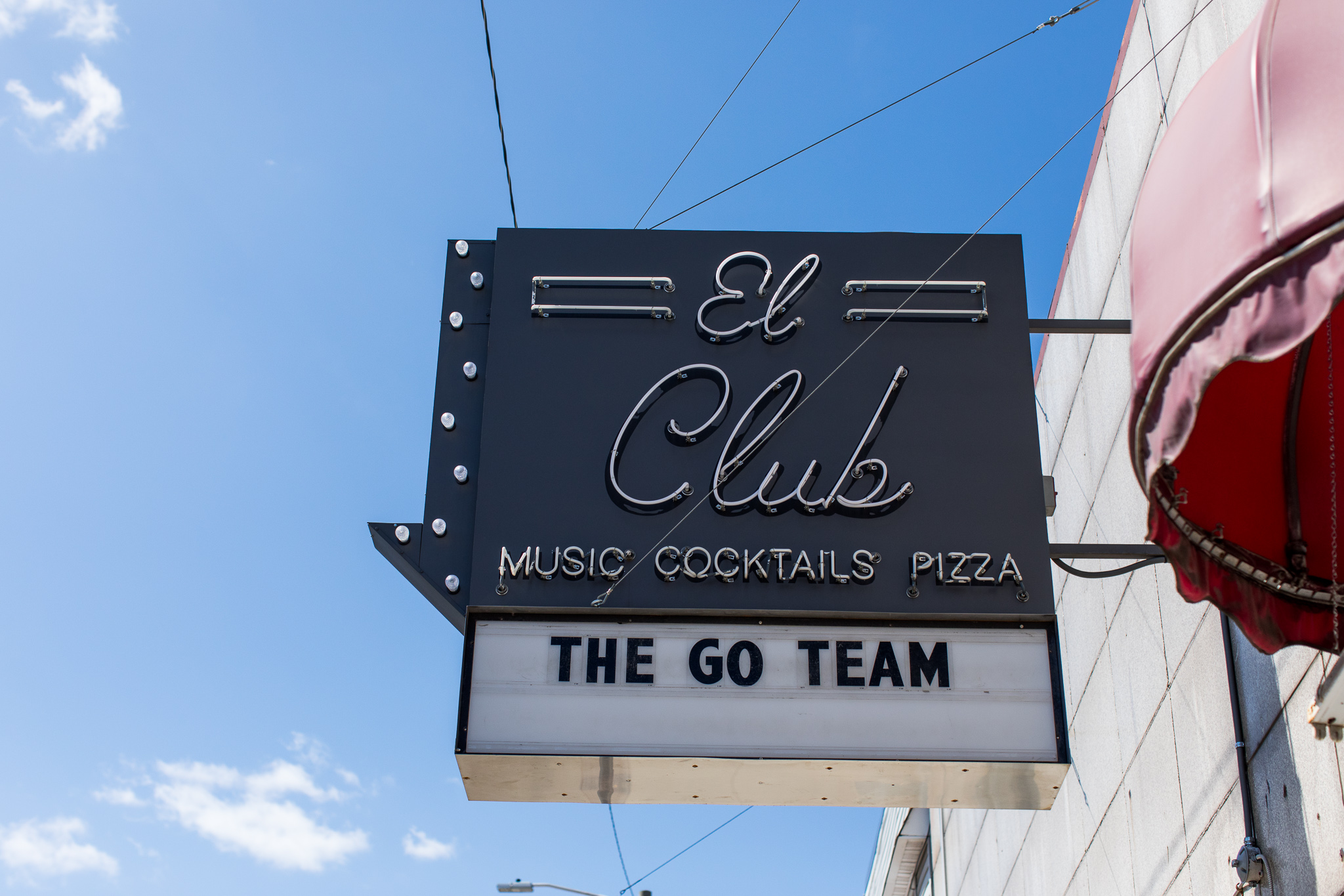 """Exterior sign hangs above El Club with a marquee that reads 'The Go Team"""""""